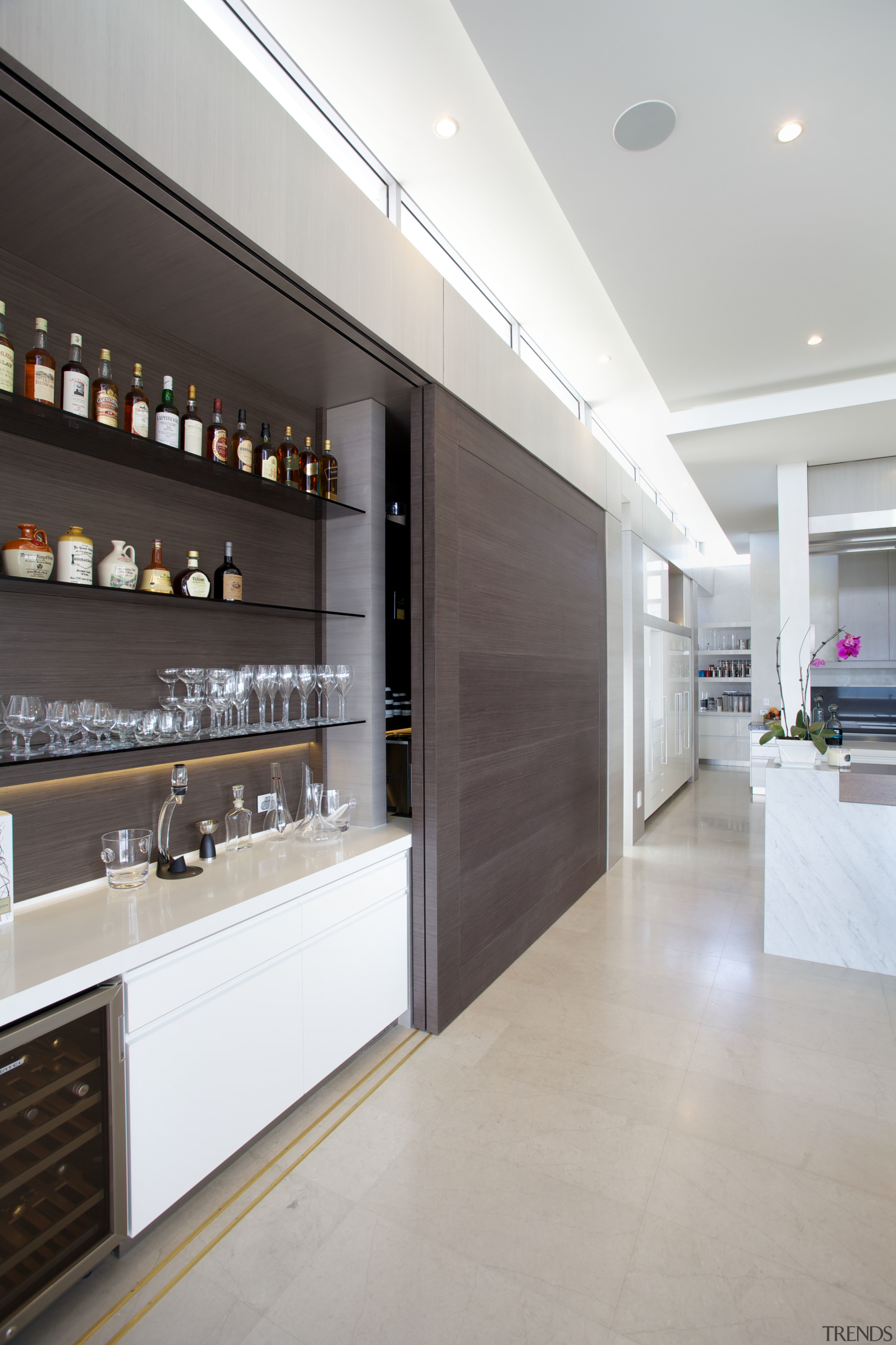Large sliding timber veneer doors conceal a fully countertop, interior design, kitchen, gray, white