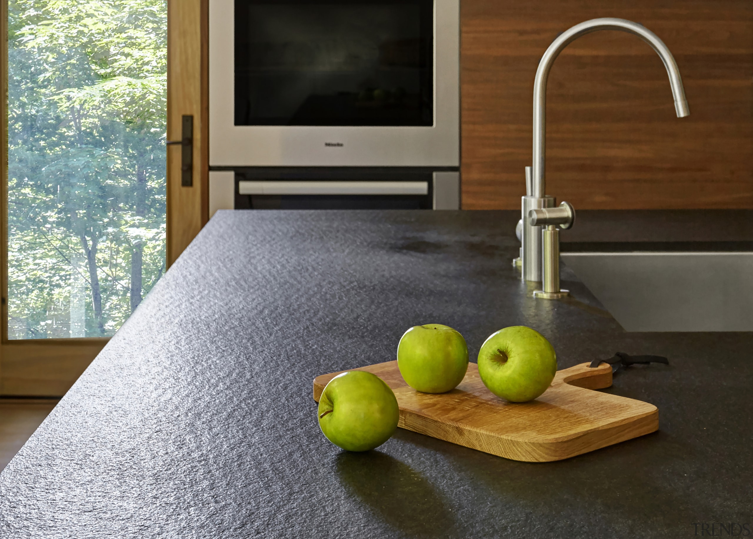​​​​​​​The brushed stone Absolute granite countertop on this countertop, floor, flooring, food, fruit, granite, hardwood, interior design, kitchen, plant, room, still life, still life photography, table, wood, black, gray