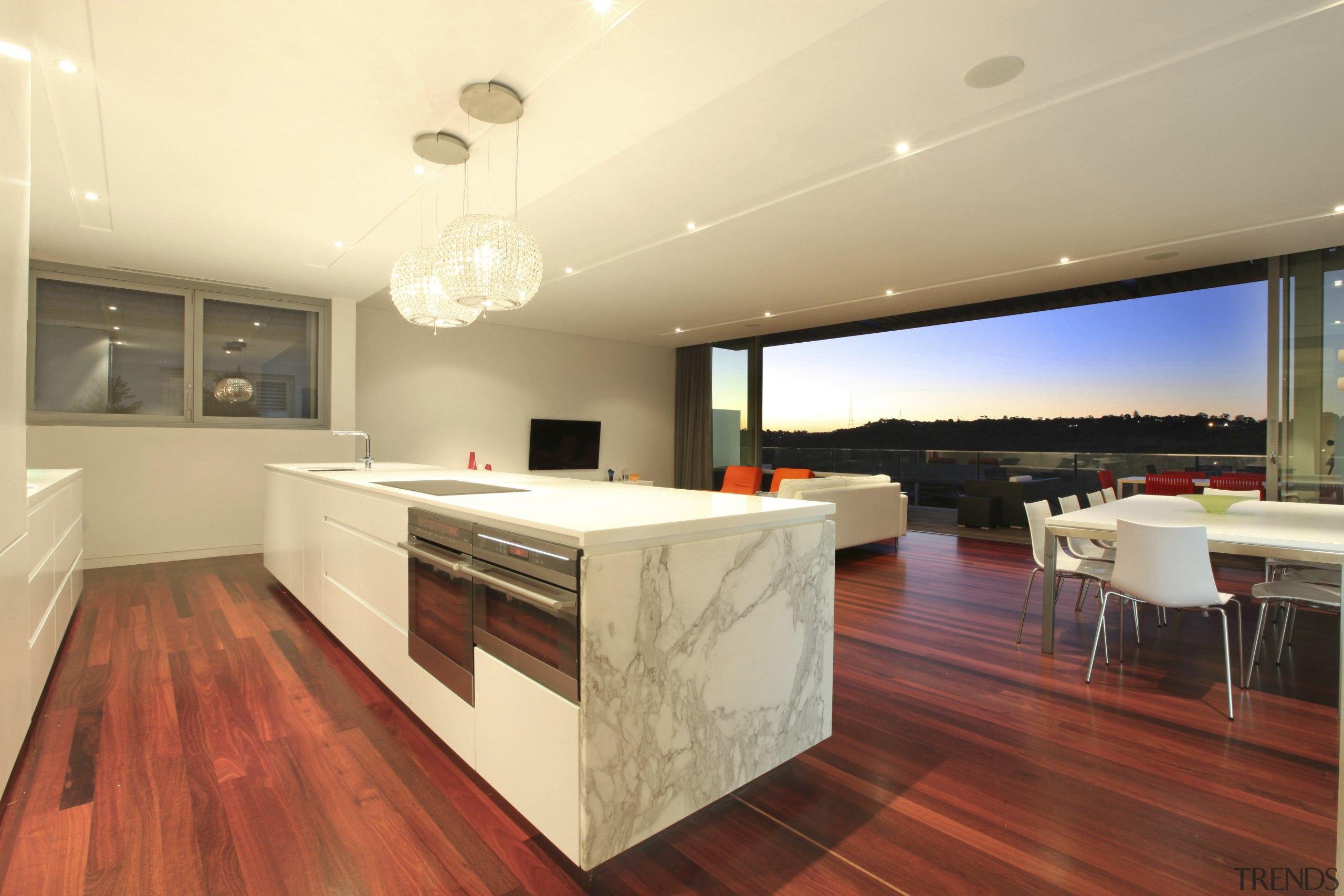 Kitchen with marble island top and wooden flooring. architecture, ceiling, countertop, floor, flooring, hardwood, interior design, kitchen, real estate, wood flooring, orange, red