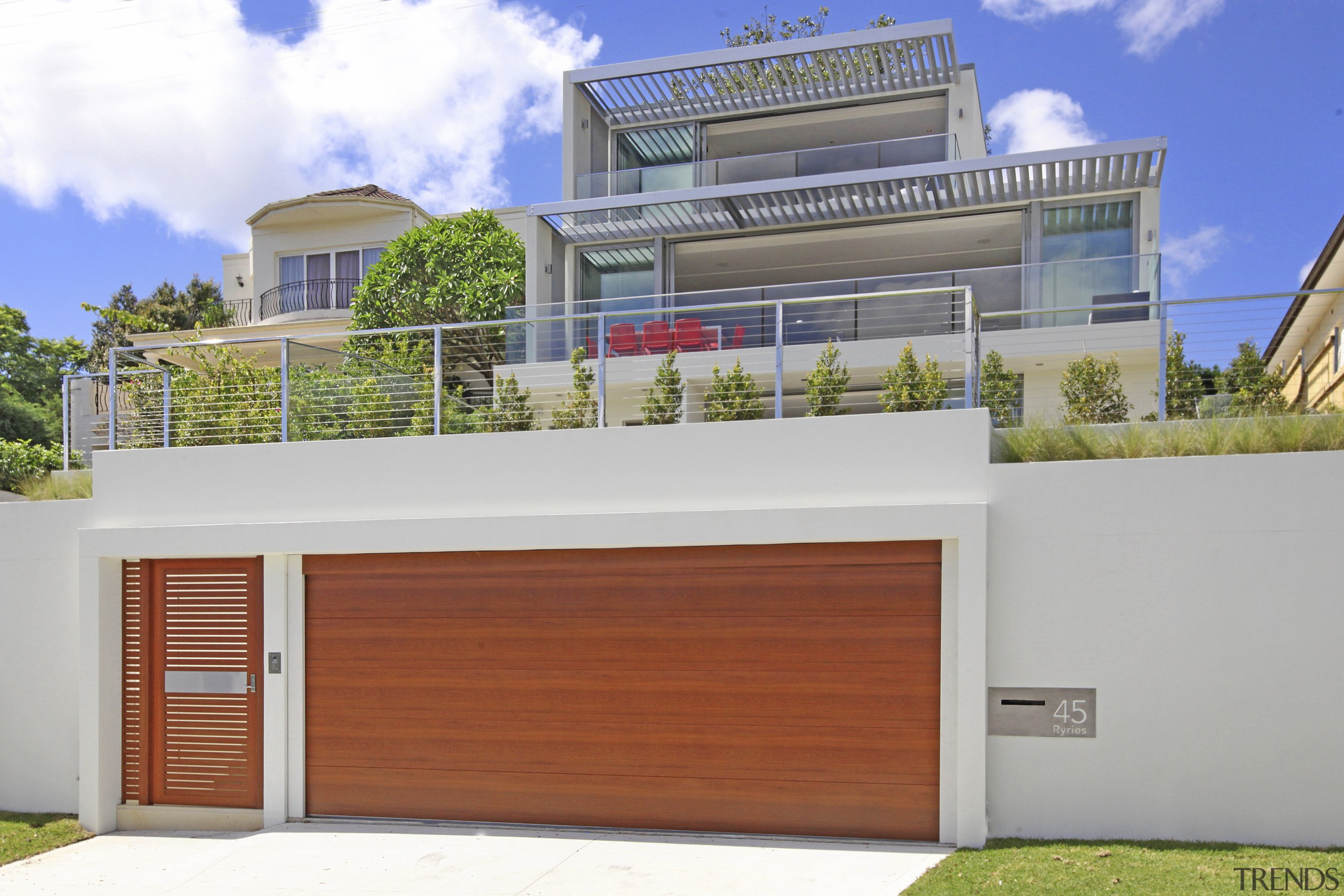 Exterior of house with wooden garage door. - architecture, building, elevation, estate, facade, home, house, official residence, property, real estate, residential area, white, gray