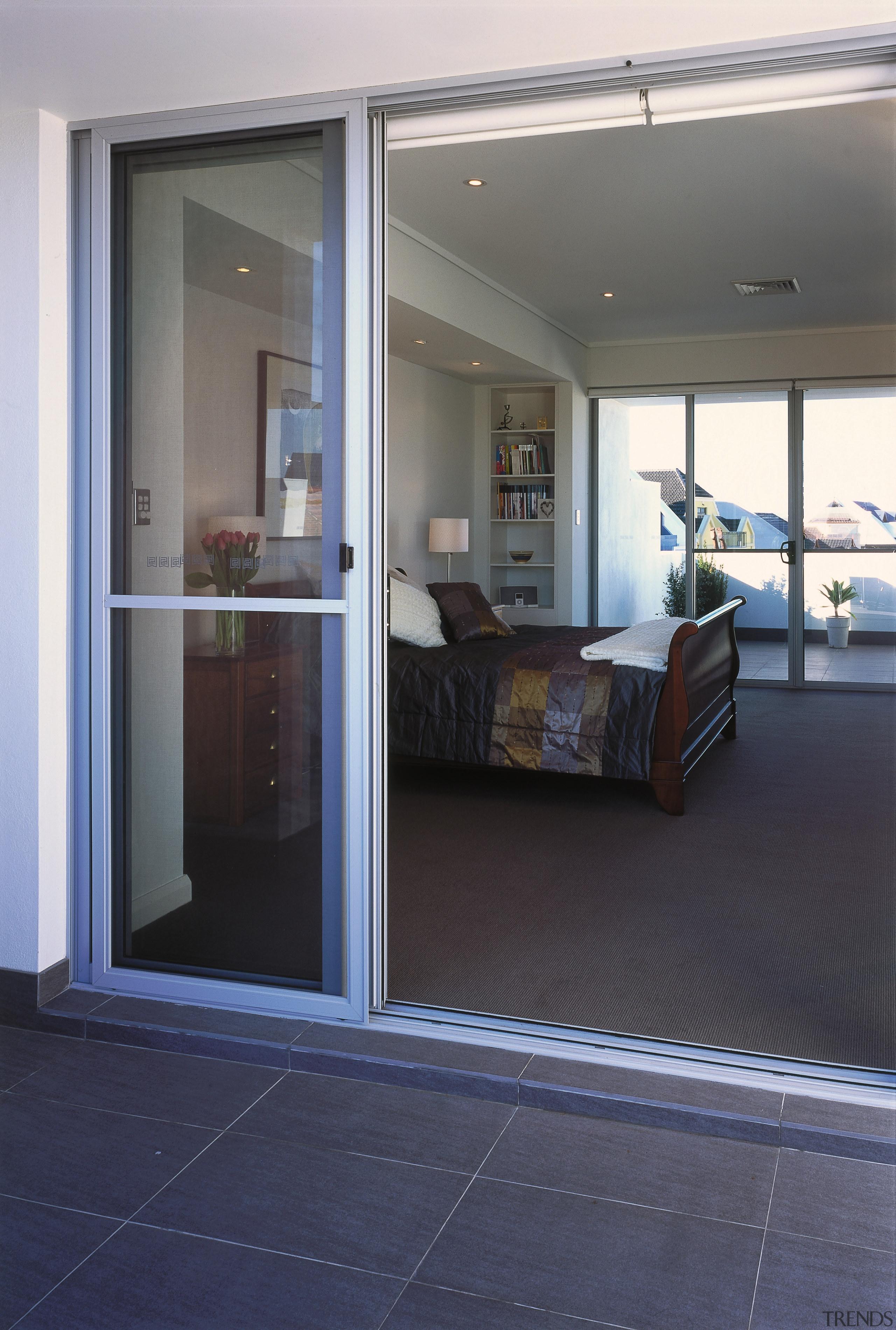 A view of the patio area. - A door, floor, flooring, glass, real estate, window, gray