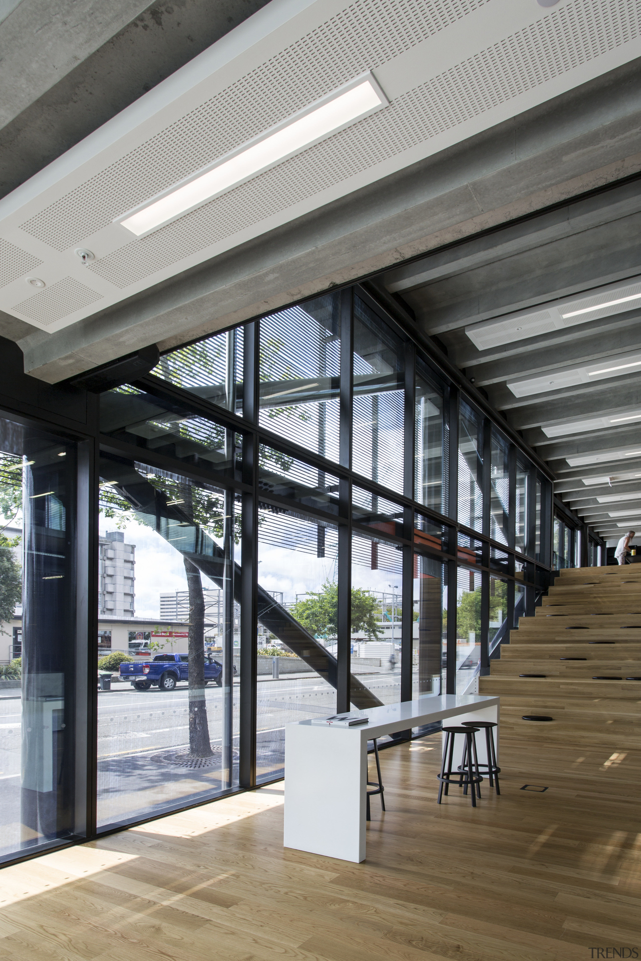 This buildings steel structure is visible from indoors ceiling, daylighting, glass, structure, window, gray