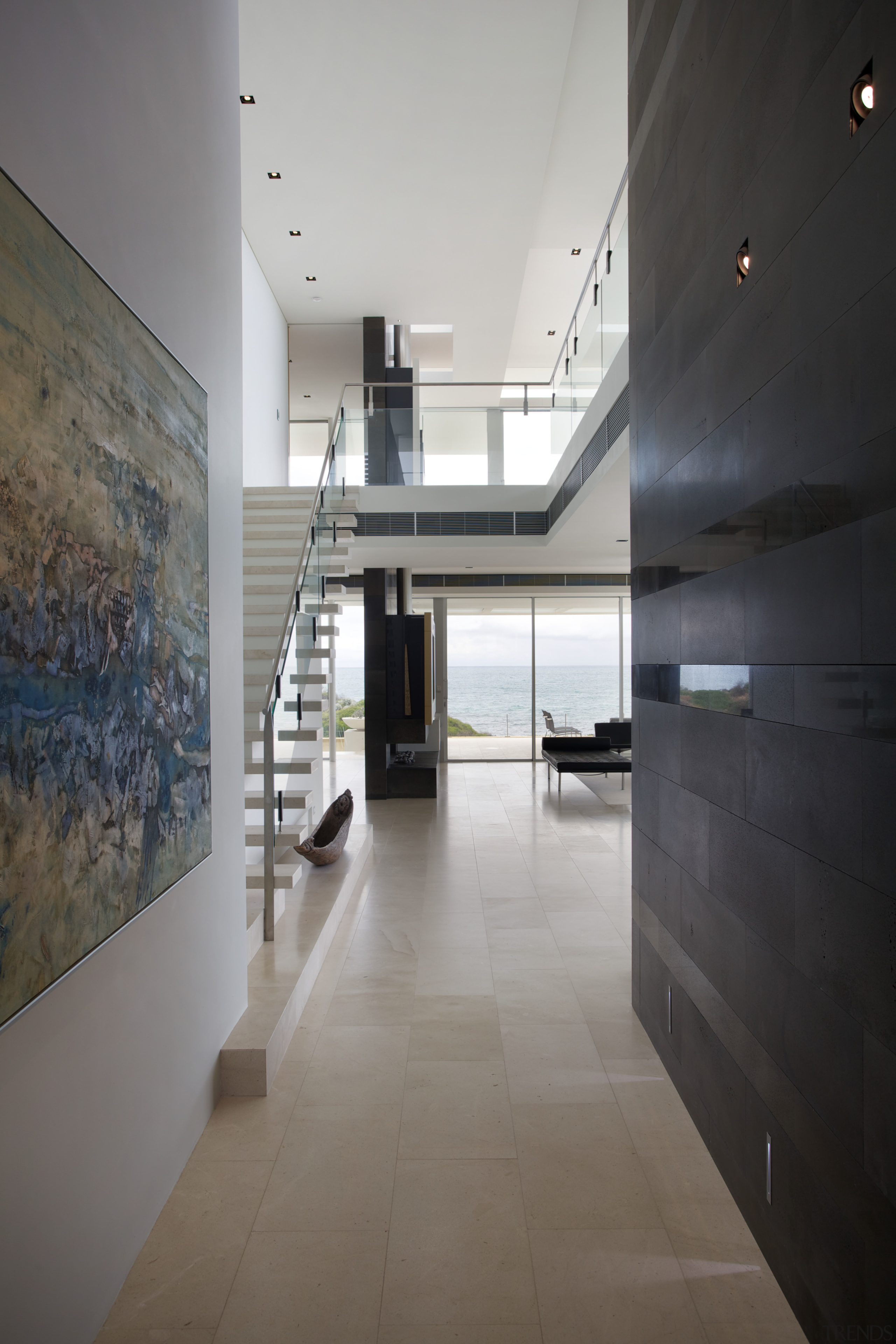 As you enter this beachside home, it opens apartment, architecture, ceiling, daylighting, floor, flooring, glass, house, interior design, lobby, tile, wood flooring, gray, black