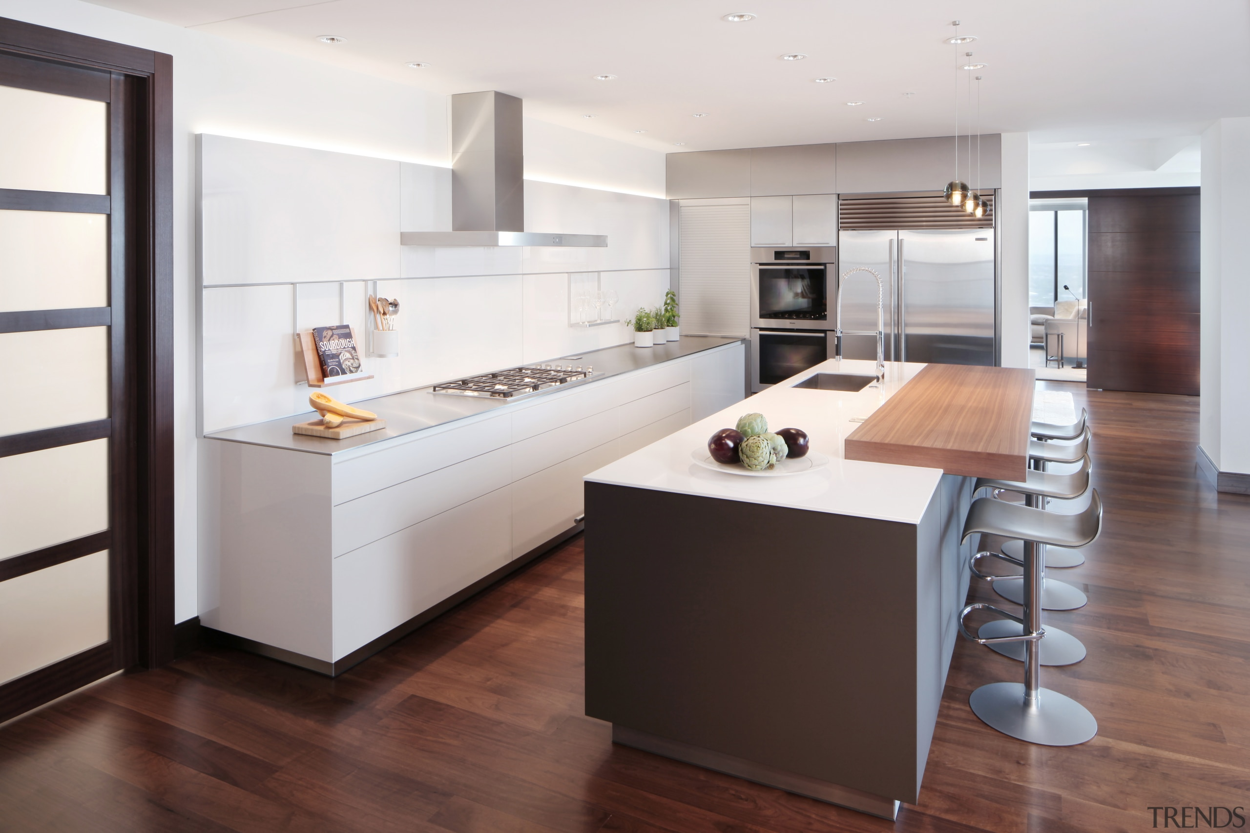 Recessed cabinetry pulls and slender countertops give this cabinetry, countertop, cuisine classique, floor, flooring, hardwood, interior design, kitchen, laminate flooring, room, wood flooring, white