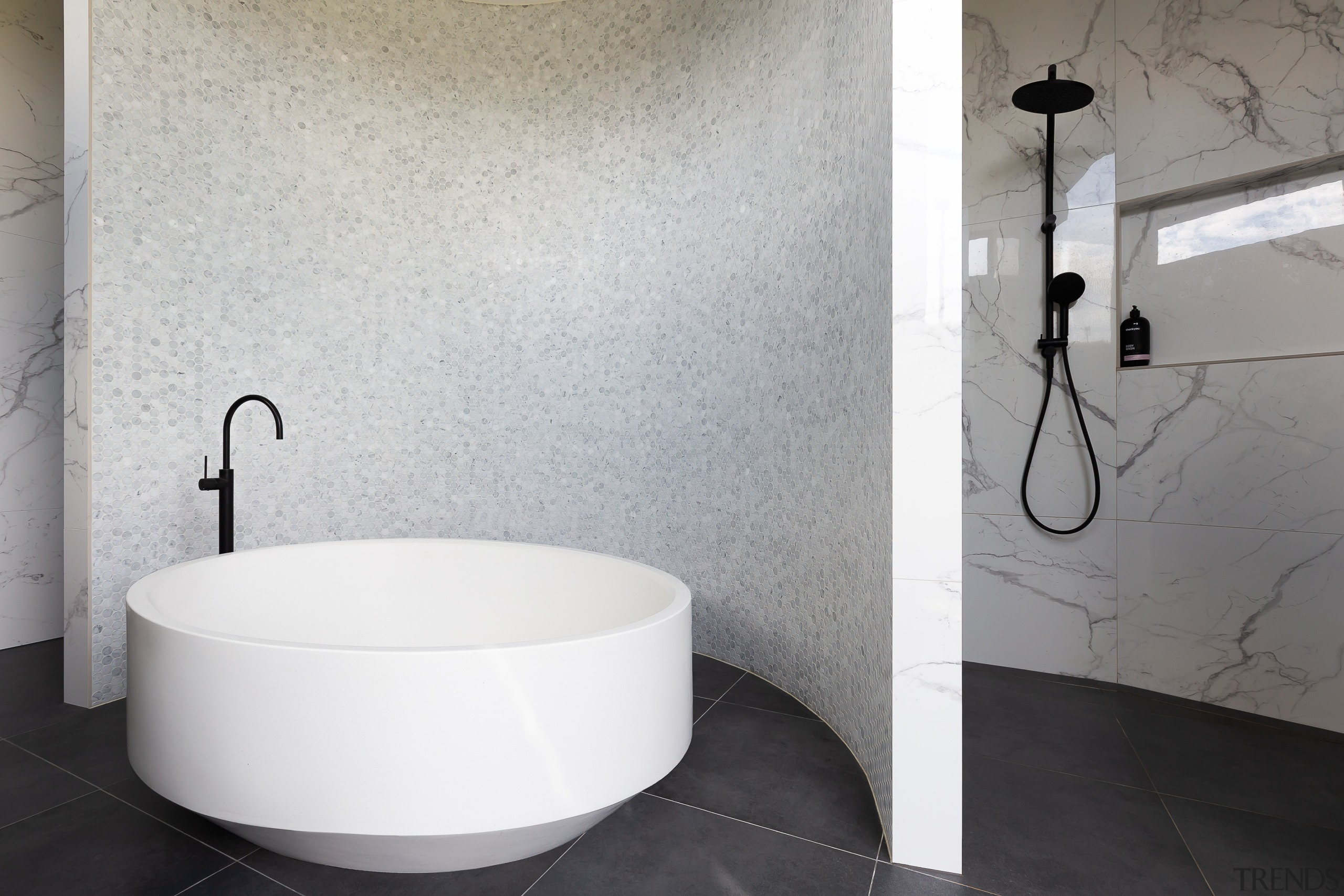 The twinkling mosaic wall behind this master bathroom's gray, white