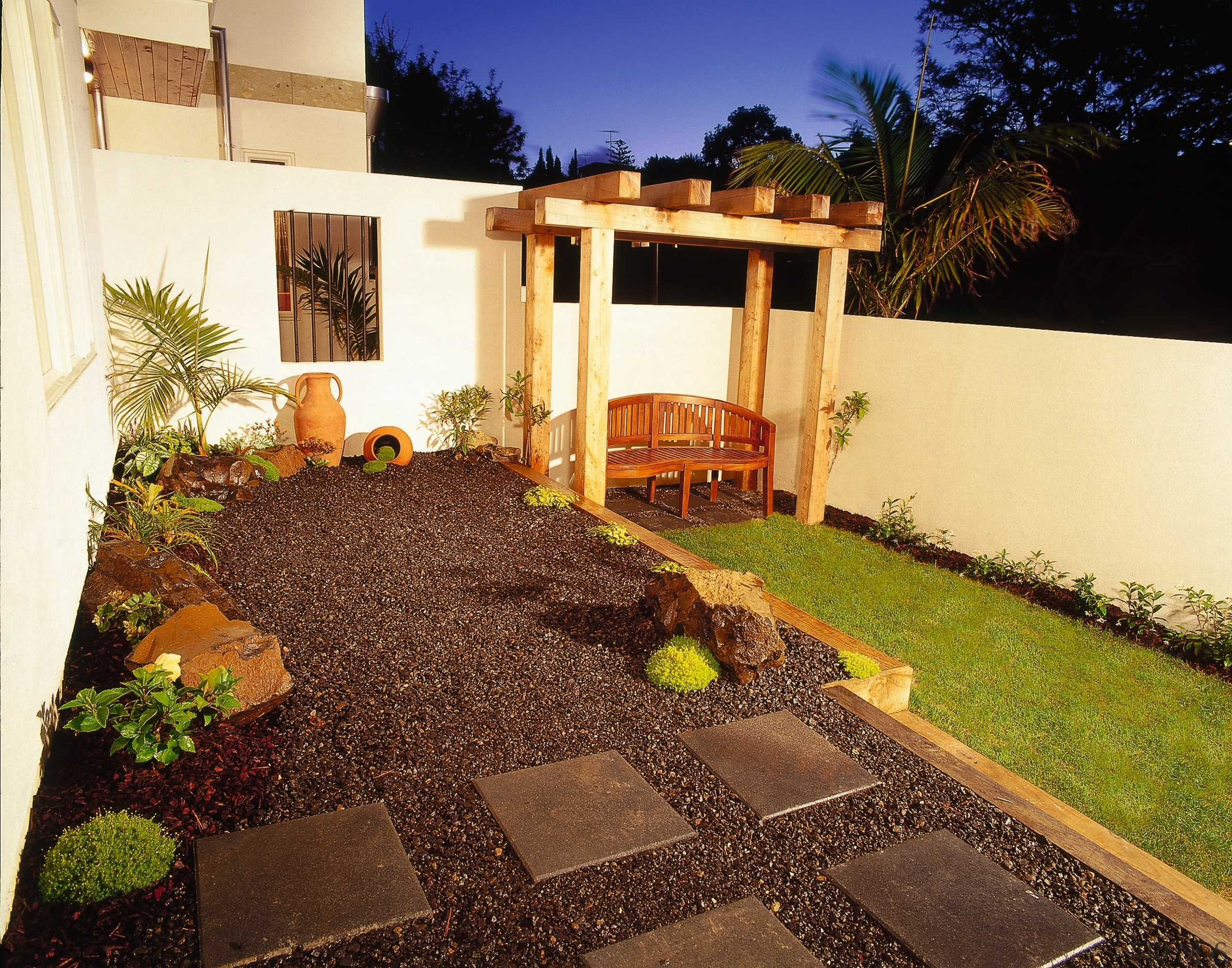 Raised Stone Chip Garden With Pavers, Rocks, Urns, Window Set In Cream  Garden Wall, Large Wooden Seat Set On Lawn Under Chunky Pergola.