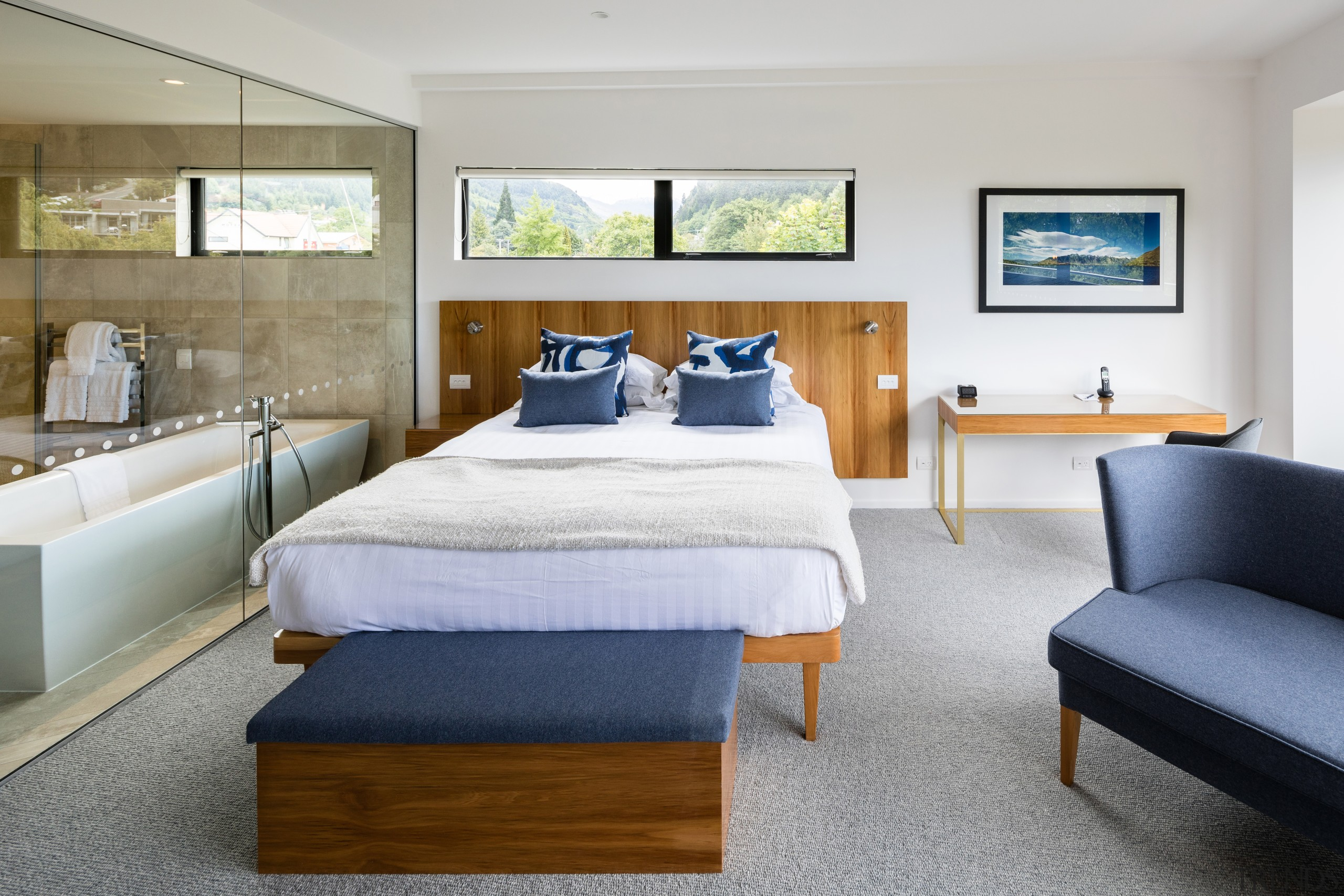 A rectangular bathtub is a modern feature within bed, bed frame, bed sheet, bedding, bedroom, boutique hotel, building, ceiling, comfort, daylighting, floor, furniture, hardwood, home, house, interior design, mattress, mattress pad, nightstand, property, real estate, room, suite, table, wall, gray
