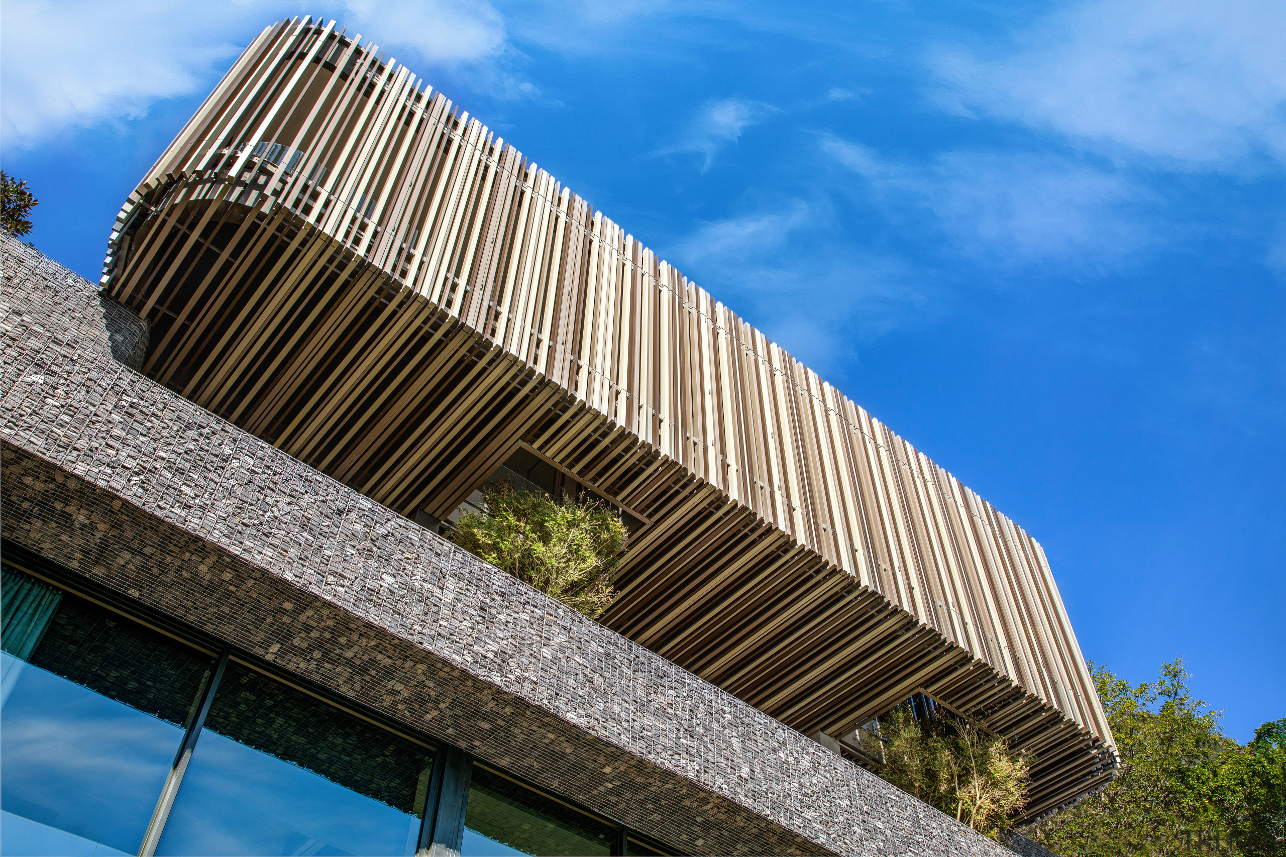 A vertically slatted box hovers over the terrace, architecture, blue, brutalist architecture, building, commercial building, daytime, facade, house, landmark, line, real estate, sky, tree