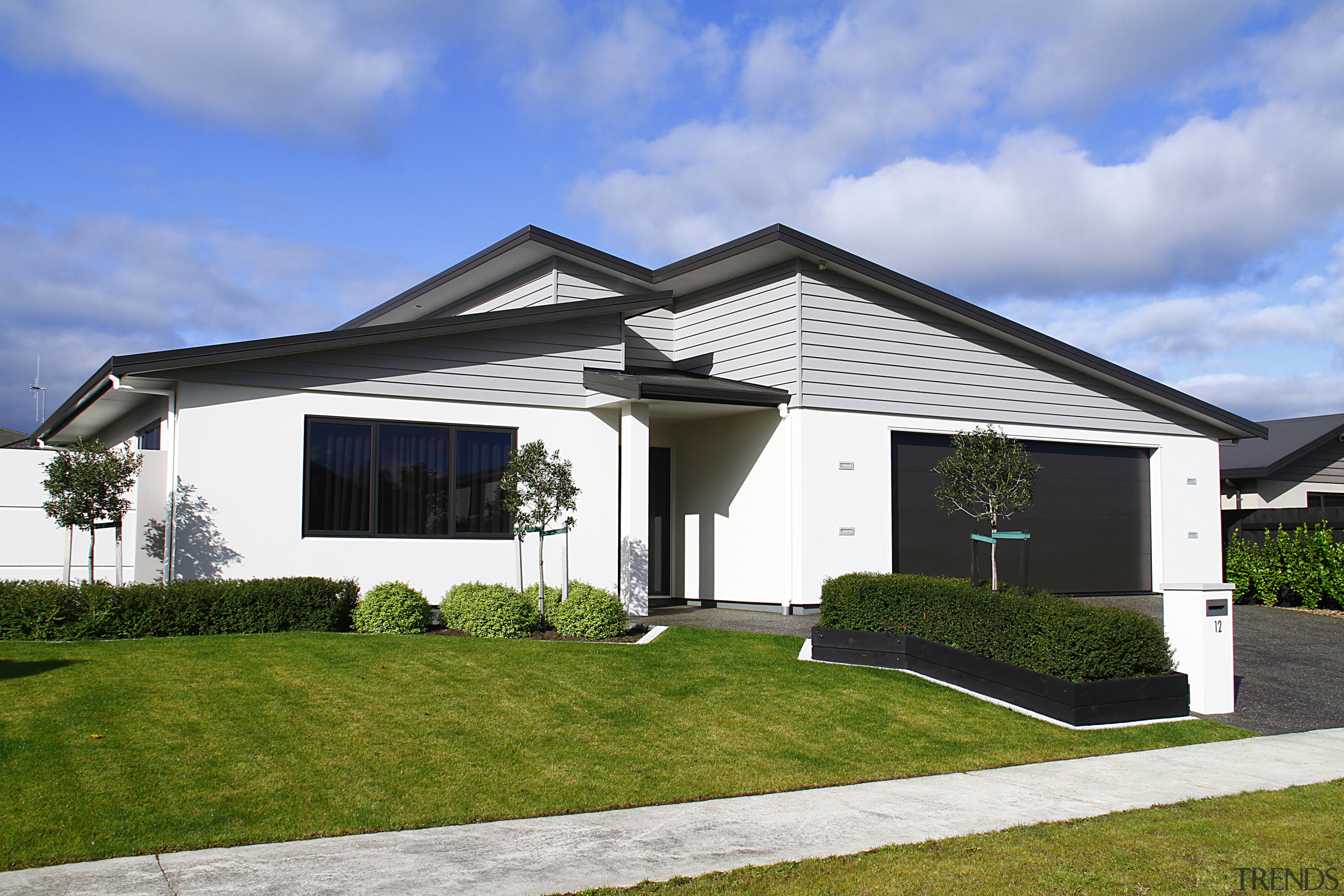 This house by Fowler Homes Manawatu features low-upkeep building, cottage, elevation, estate, facade, home, house, property, real estate, residential area, roof, siding, sky, villa, teal, white