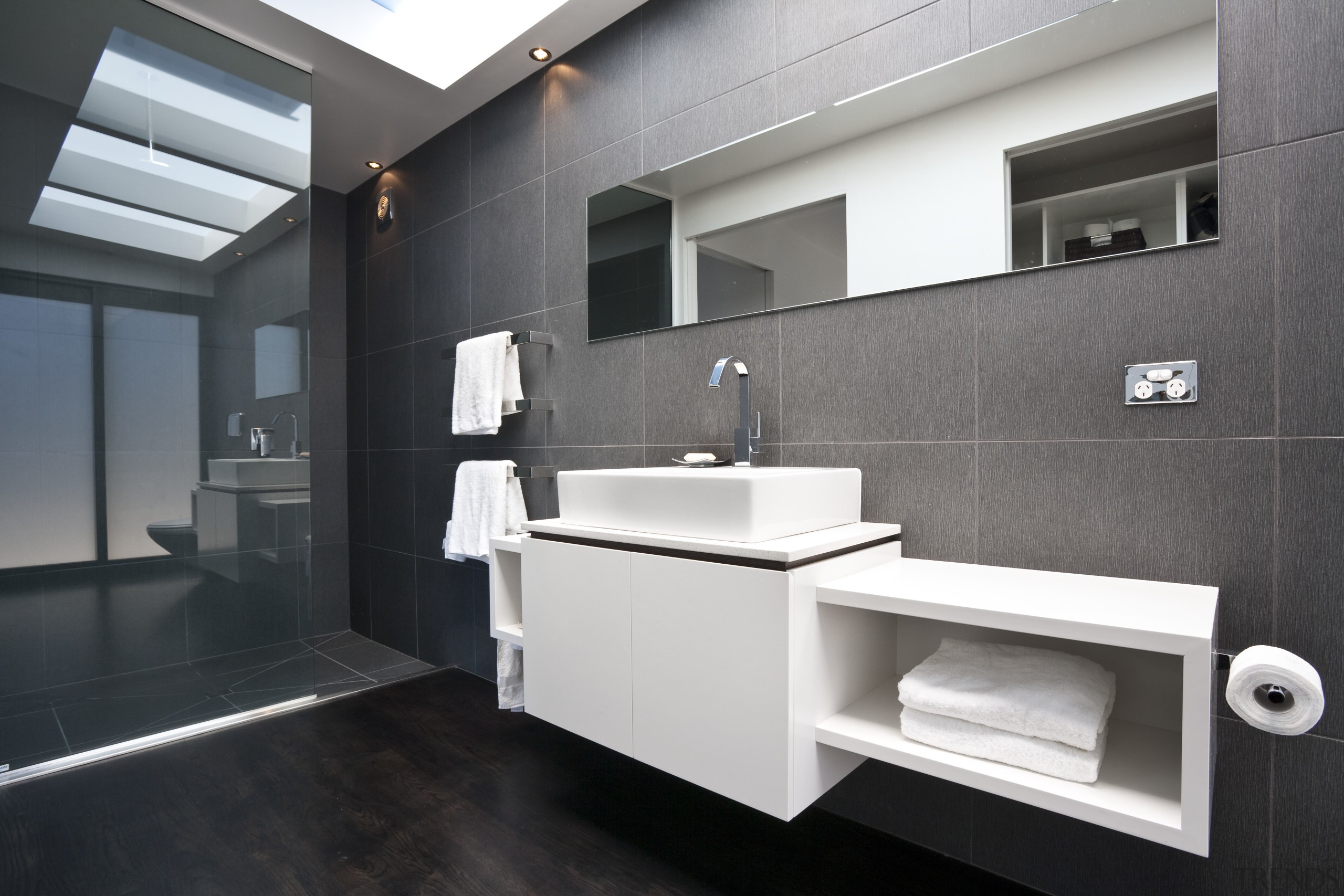 View of the bathroom featuring white cabinetry and architecture, bathroom, bathroom accessory, floor, interior design, product design, room, sink, black, gray