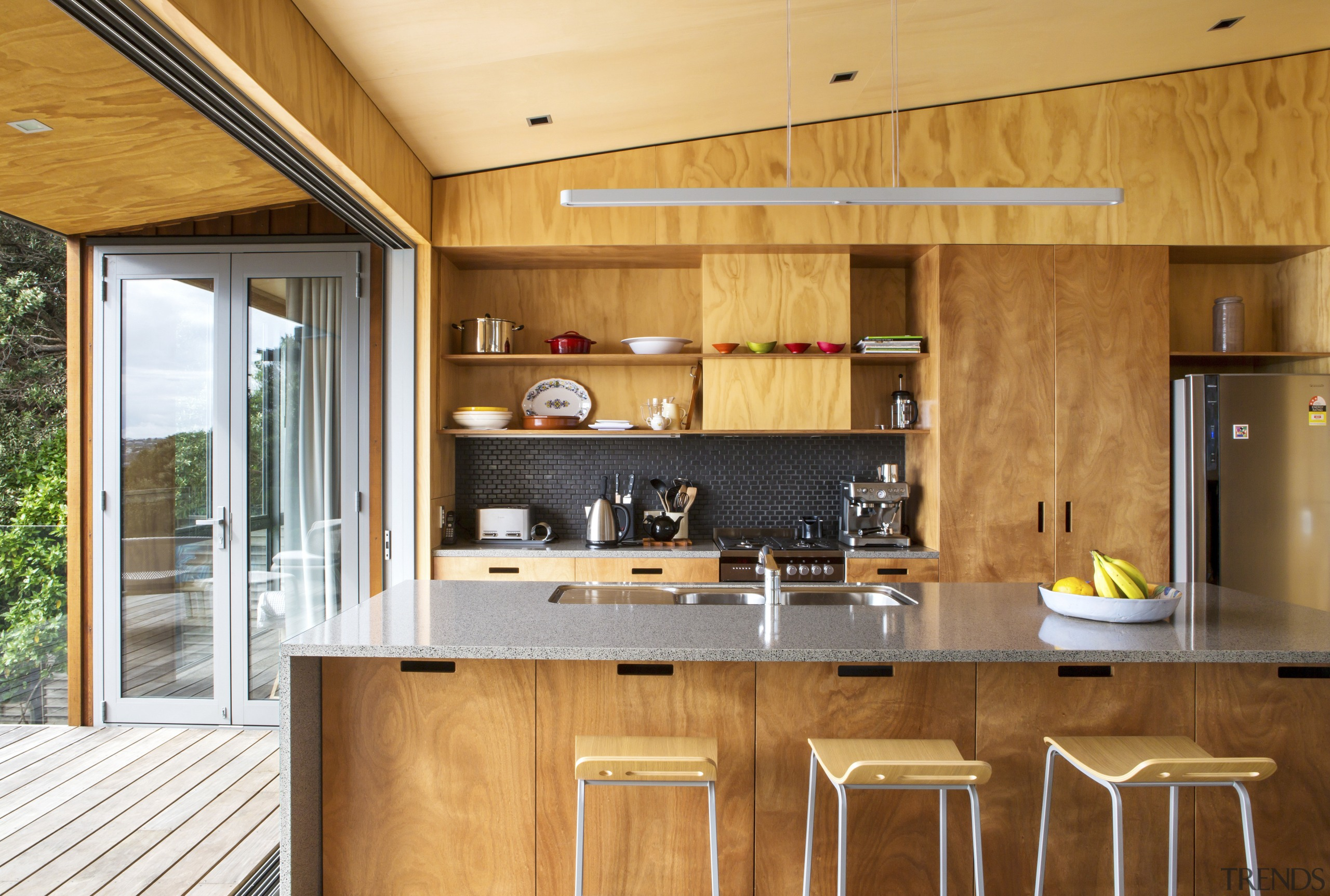 The island in this holiday home by Box architecture, cabinetry, countertop, cuisine classique, house, interior design, kitchen, real estate, wood, orange, brown