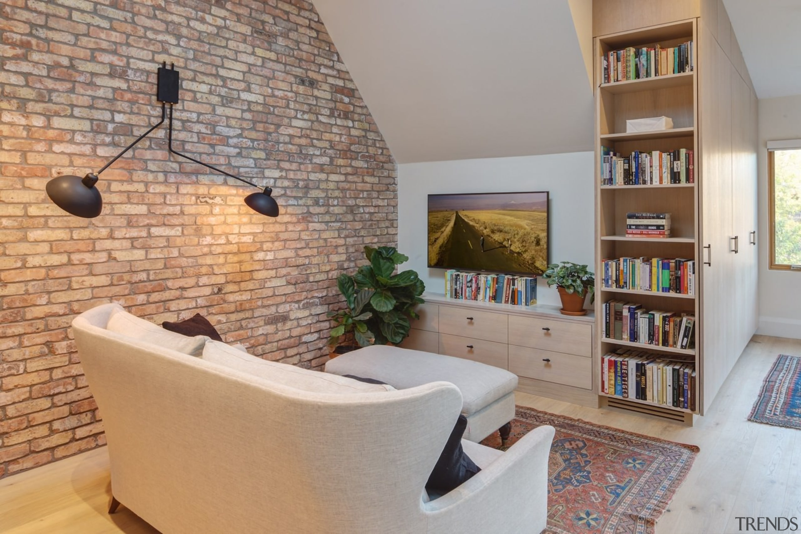 A large brick wall acts as a strong floor, flooring, furniture, home, interior design, living room, real estate, room, shelf, shelving, wall, gray