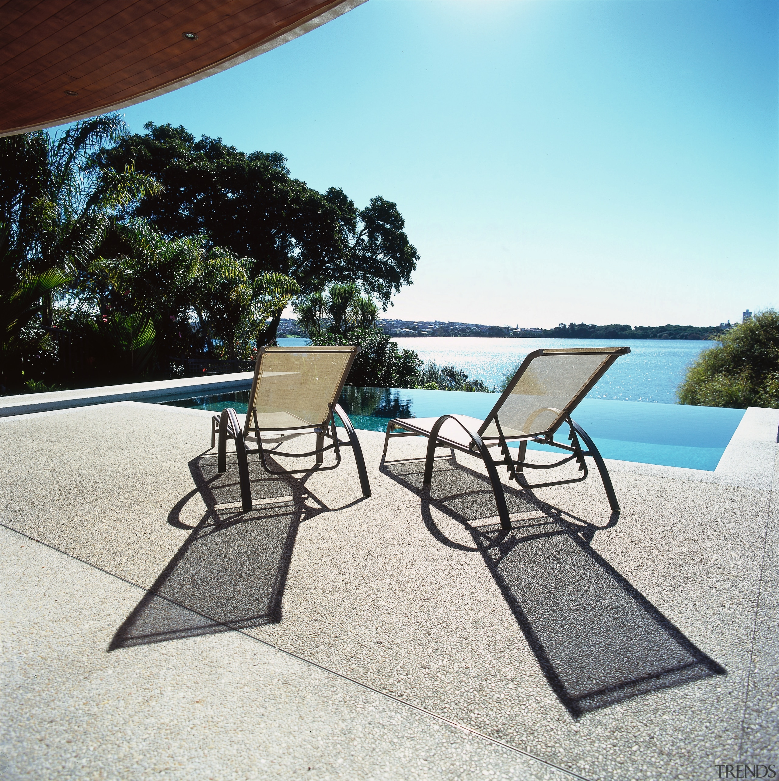 Pool with wet edge looking out to lake, chair, estate, floor, furniture, leisure, outdoor furniture, outdoor structure, property, real estate, sunlounger, swimming pool, table, vacation, water, white