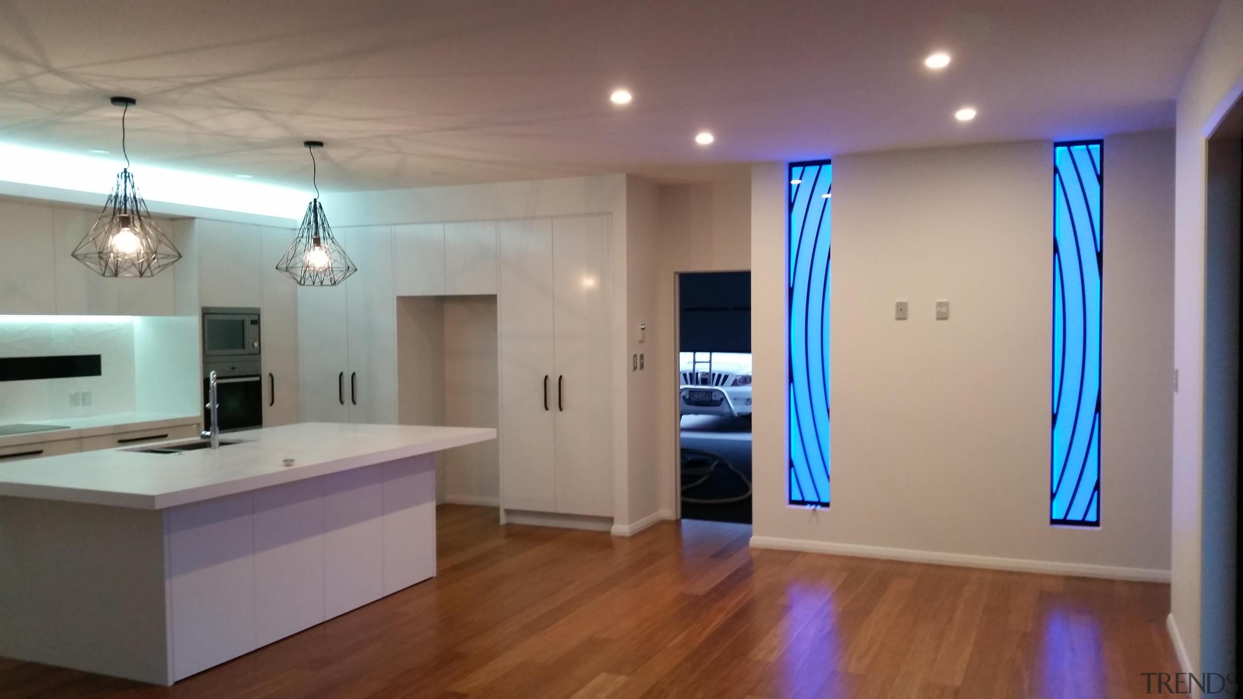 Colourful glass splashbacks create a dynamic backdrop in ceiling, floor, flooring, hardwood, home, interior design, lighting, property, real estate, room, wood flooring, gray