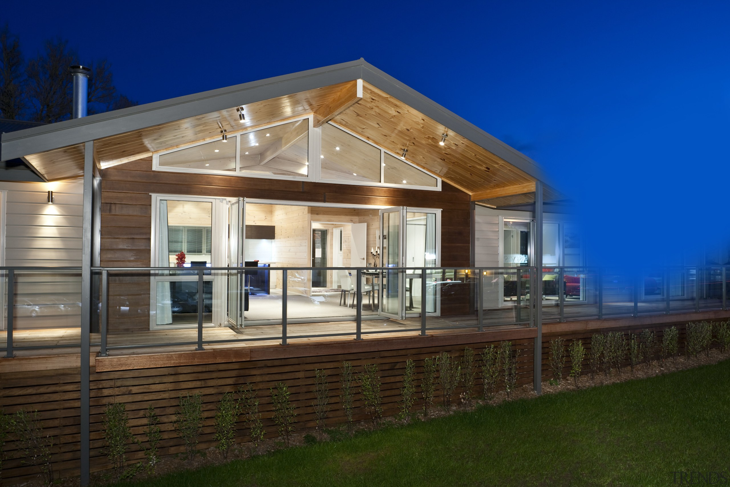 Exterior view of this contemporary home - Exterior architecture, cottage, elevation, facade, home, house, lighting, real estate, residential area, siding, sky, window, brown, blue