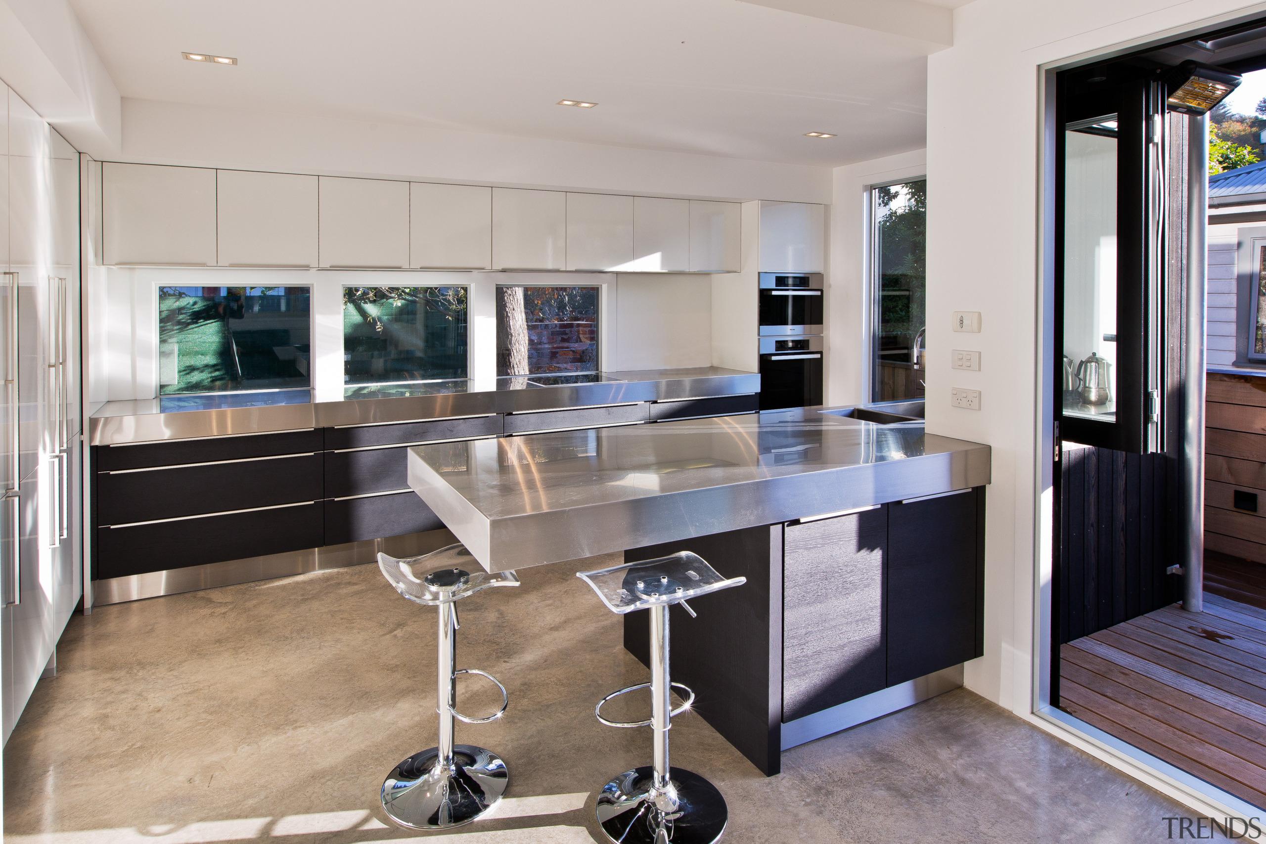 This kitchen by designer Milvia Hannah responds to countertop, floor, interior design, kitchen, real estate, gray