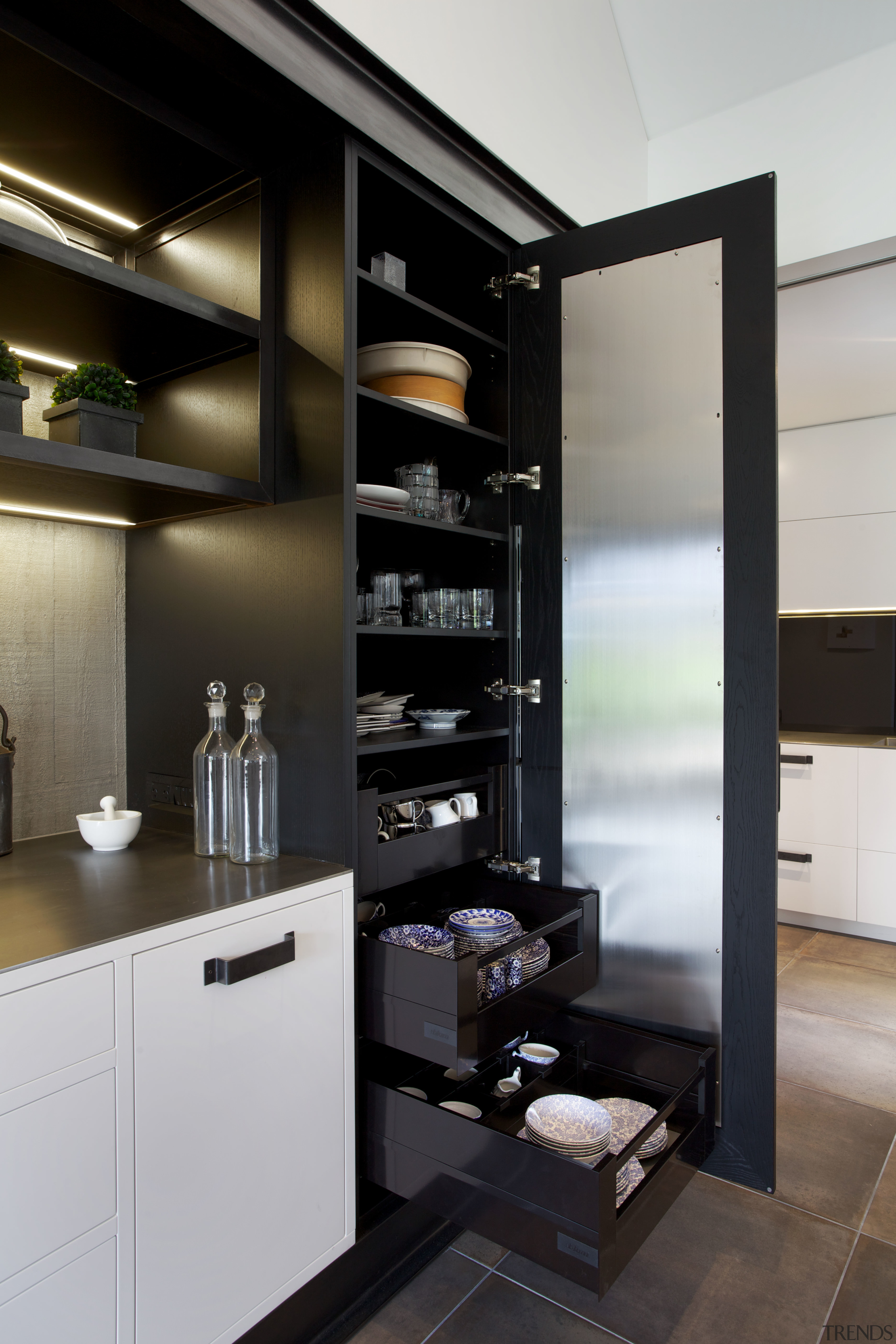 Storage is provided in tall cabinets either side furniture, interior design, kitchen, black, gray