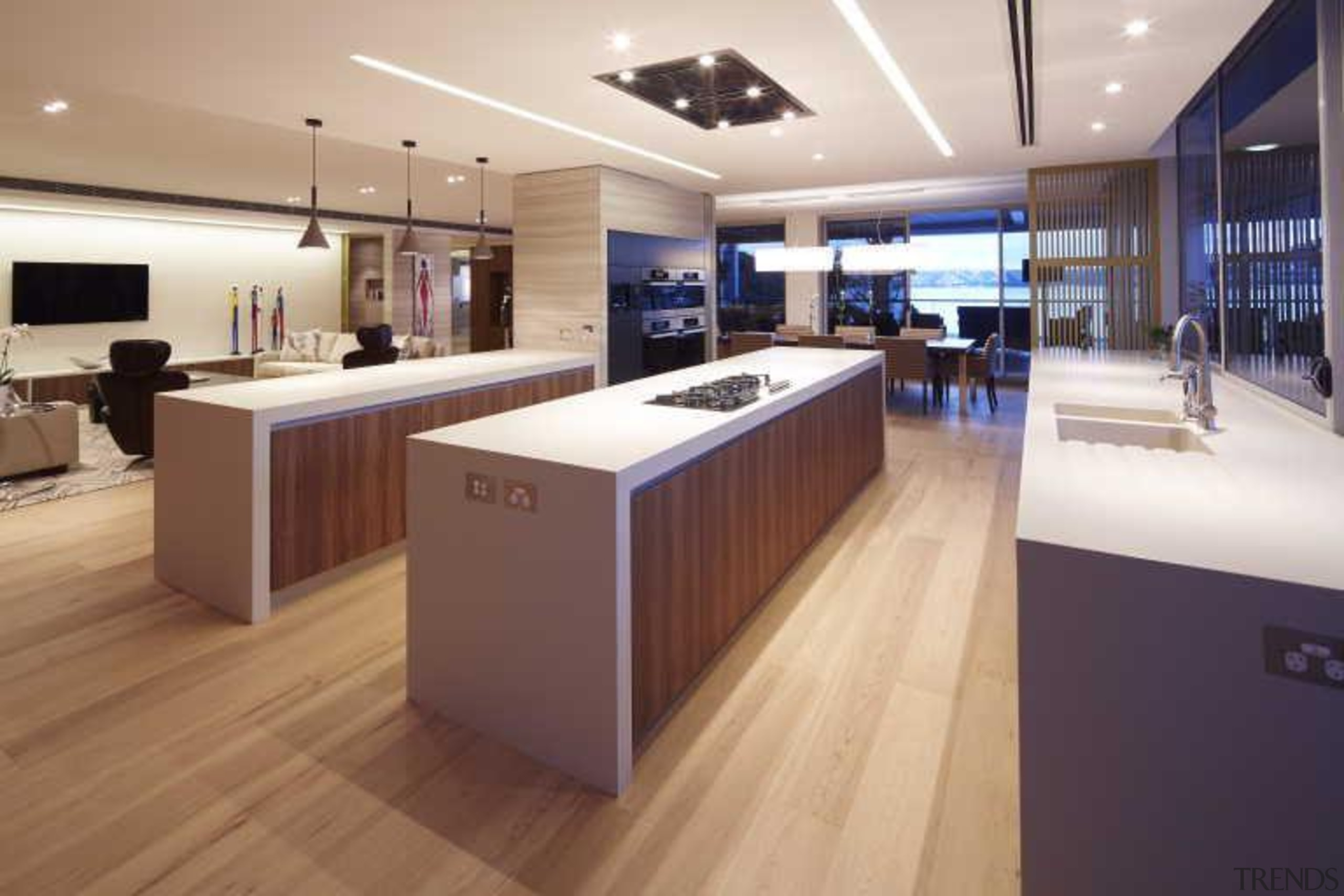 In this contemporary apartment renovation, woodgrain surfaces from countertop, floor, flooring, hardwood, interior design, kitchen, wood, white