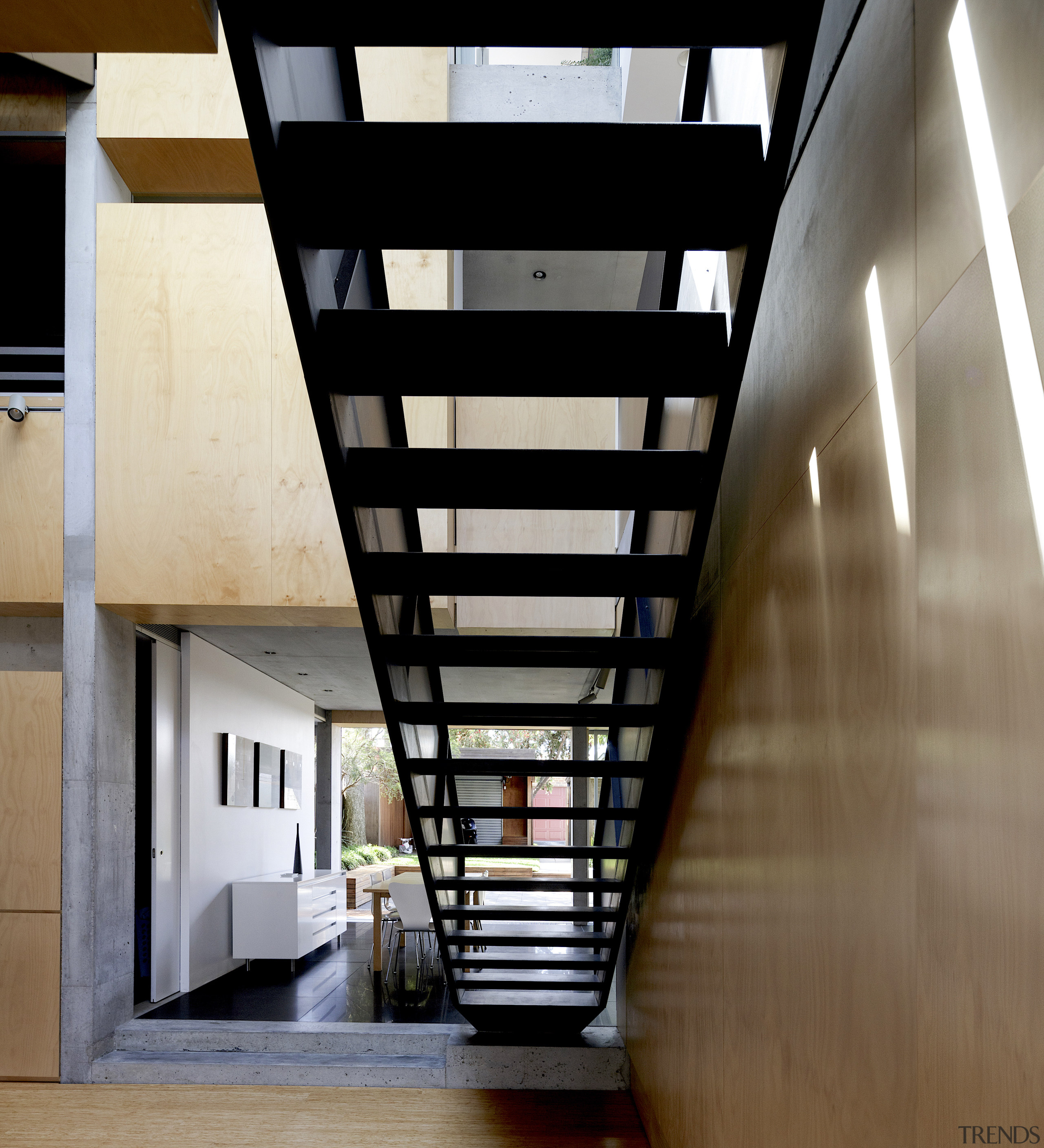 The black steel staircase acts as a bridge