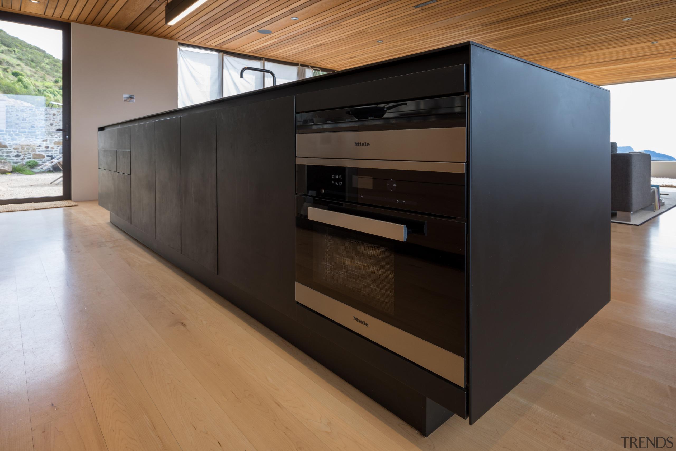 The main black surface is viewed on entering floor, flooring, furniture, wood, black, brown