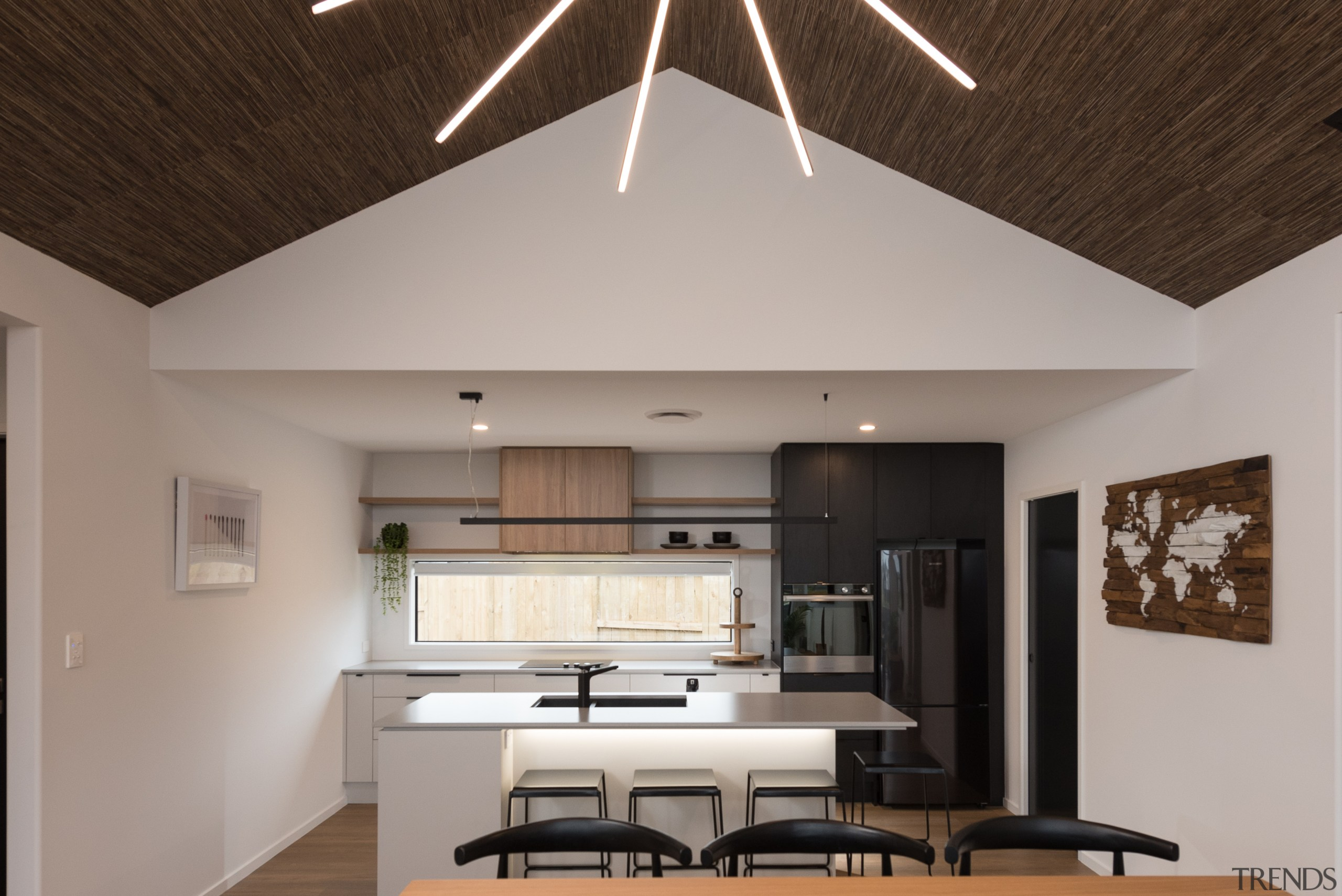 A dropped ceiling helps define the kitchen beside