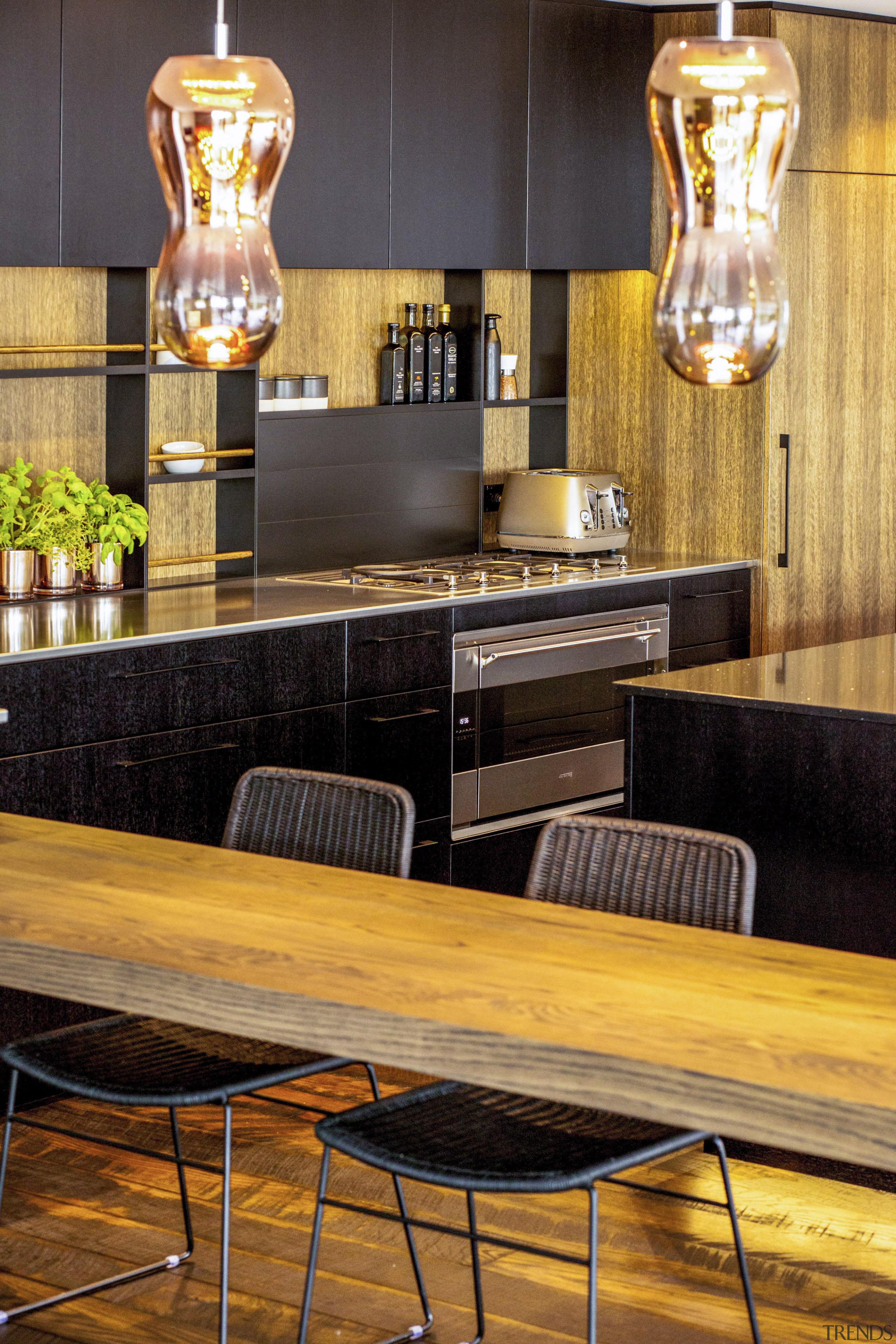 A sleek Smeg oven and cooktop were chosen furniture, interior design, restaurant, table, wood, orange, black