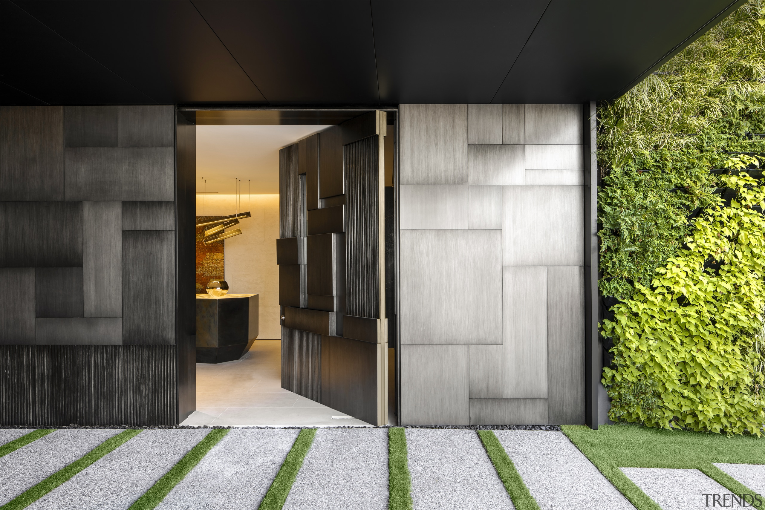 A custom designed pivoting front door sits beside