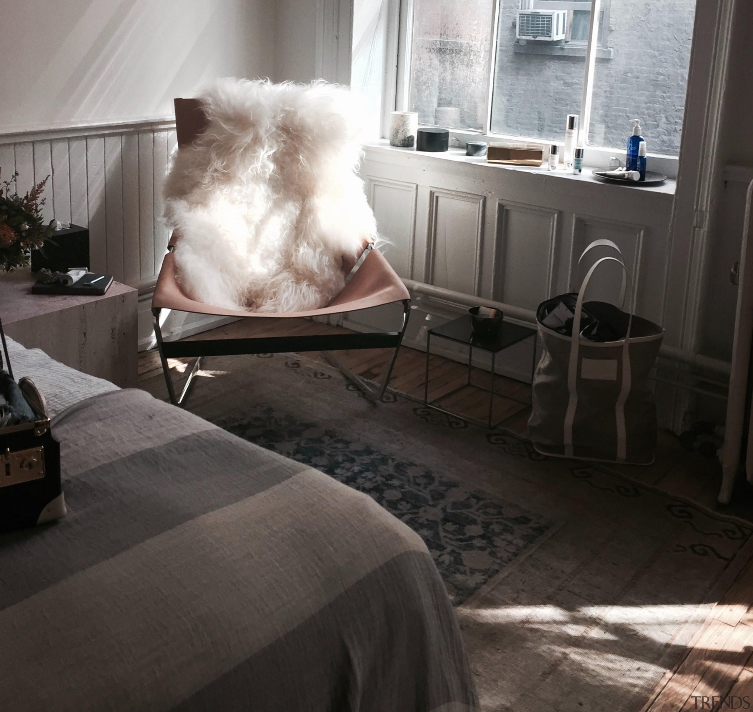 Sheepskin rug on chair in bedroom -