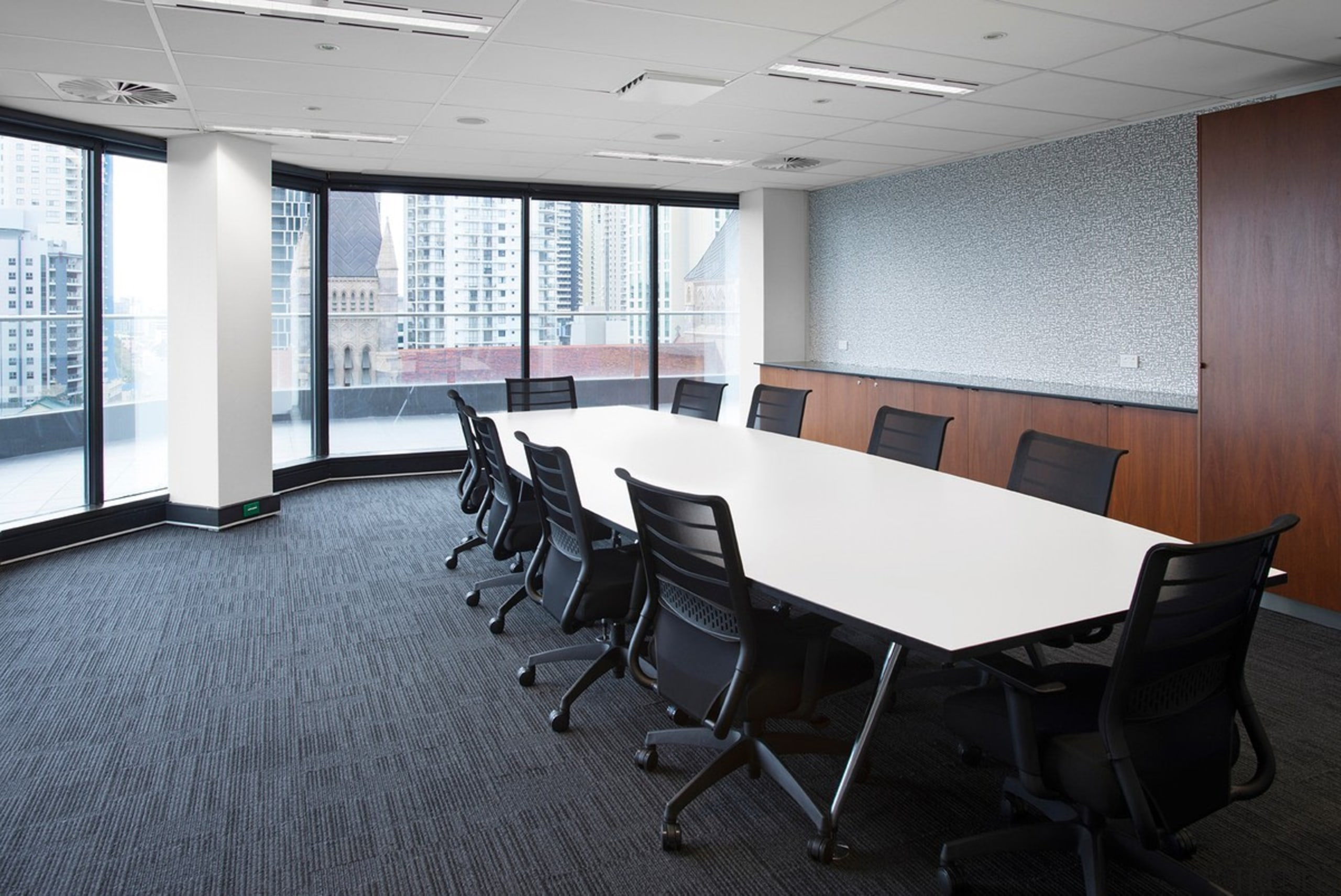 This long meeting room features expansive city views conference hall, floor, flooring, furniture, interior design, office, real estate, table, gray, white, black