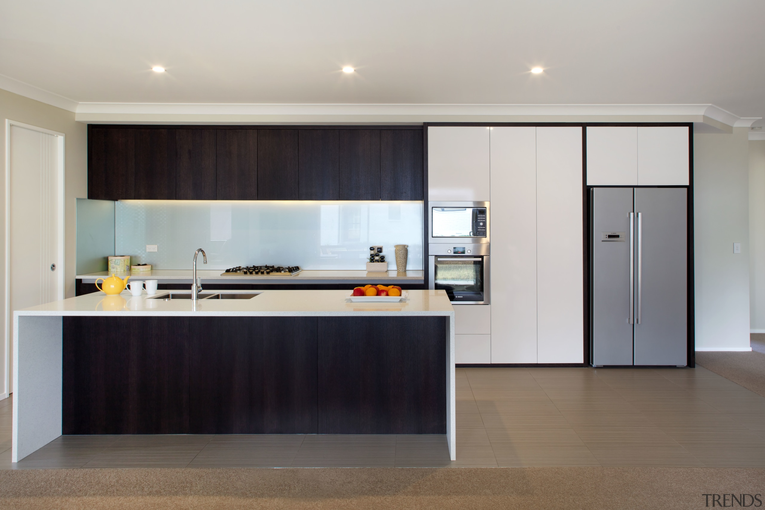 A two-tone colour palette brings a touch of architecture, cabinetry, countertop, floor, flooring, interior design, kitchen, real estate, room, gray