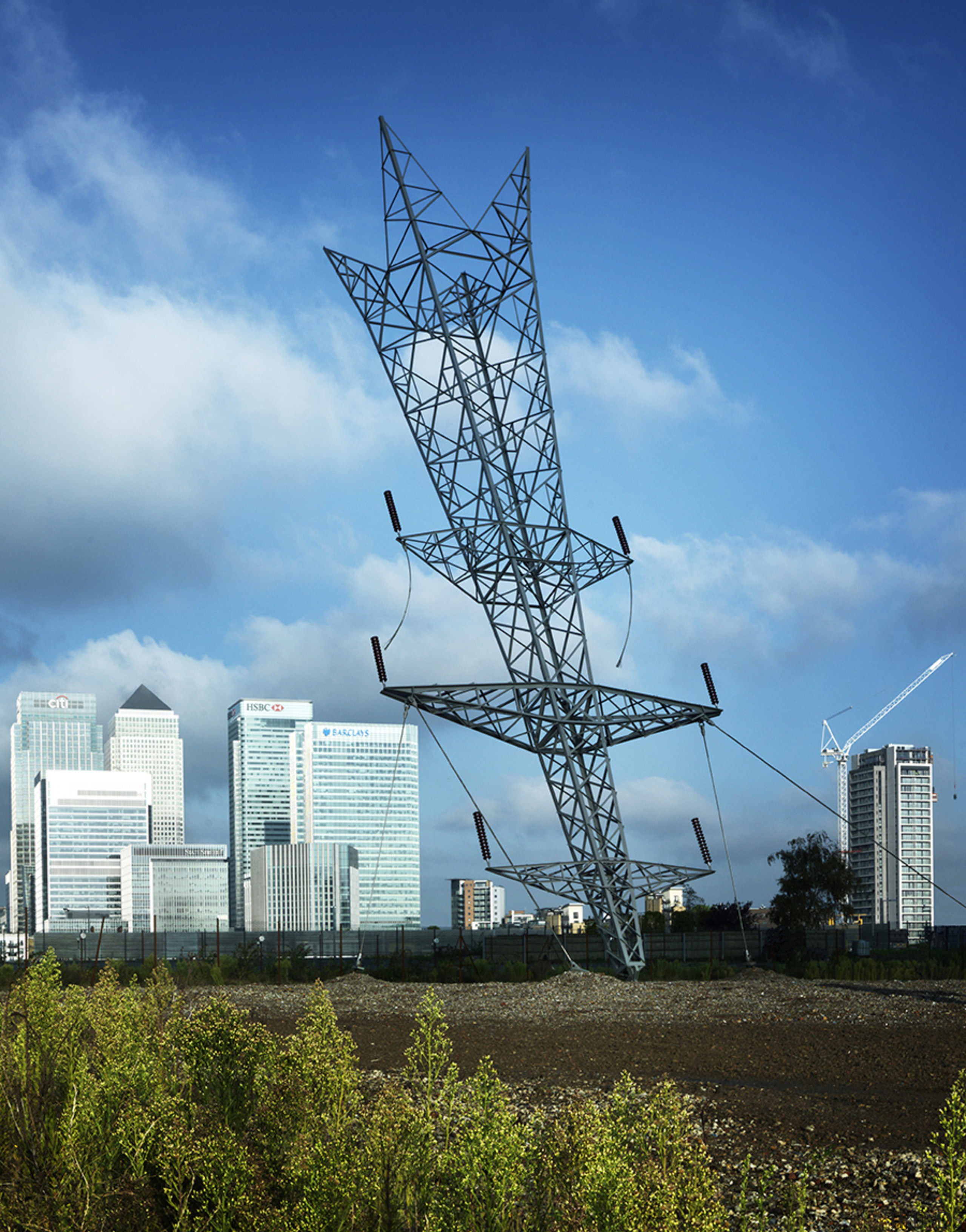 Alex Chinneck – A bullet from a shooting architecture, city, cloud, electrical supply, electricity, infrastructure, line, metropolitan area, overhead power line, public utility, residential area, sky, tower, tower block, transmission tower, tree, urban area, teal, blue