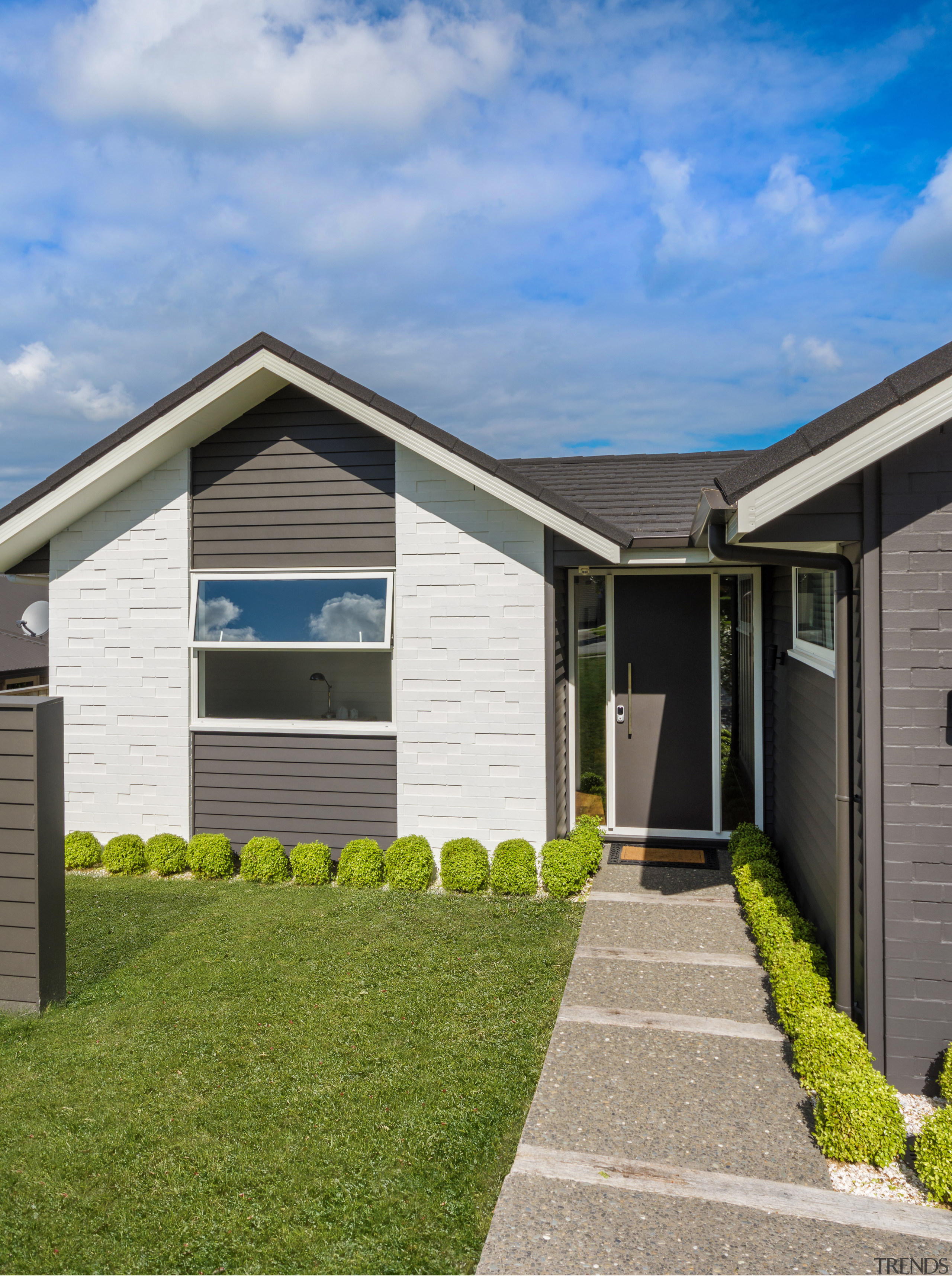 Clad in painted brick and weatherboard, this Landmark cottage, elevation, estate, facade, grass, home, house, property, real estate, residential area, shed, siding, sky, window, yard, teal