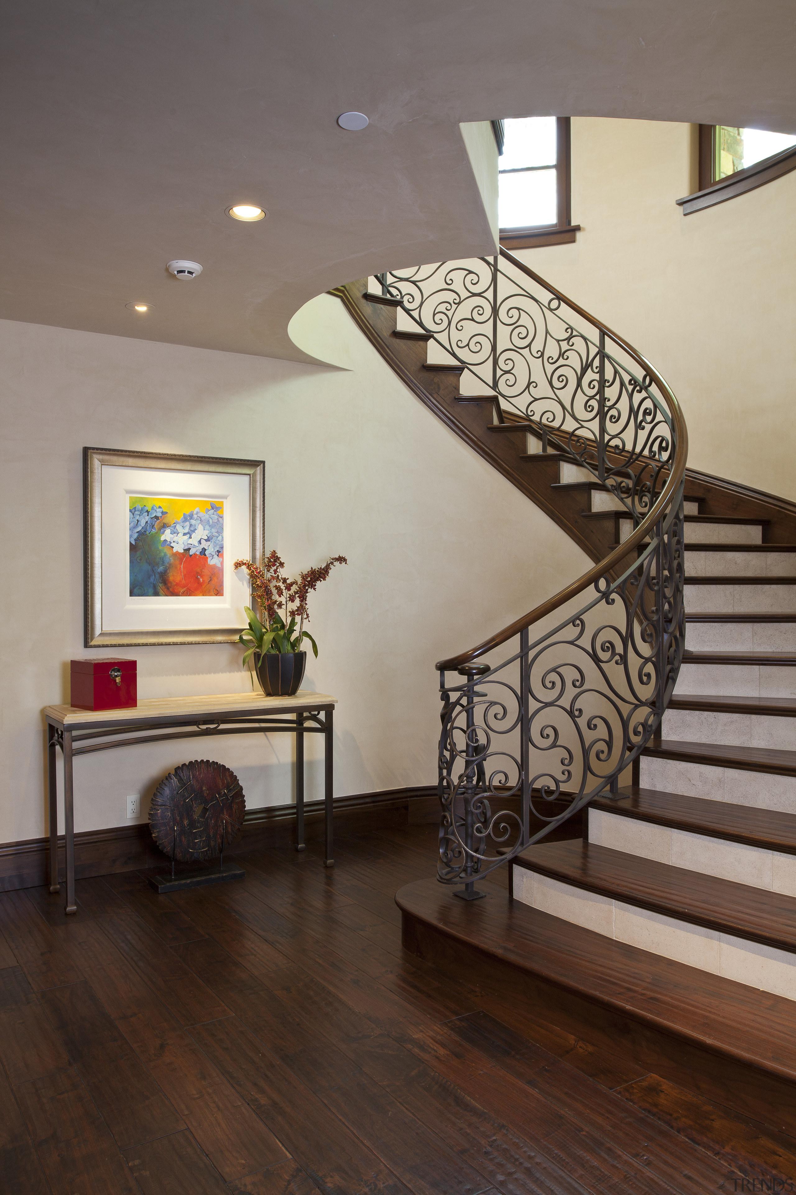 A custom scroll pattern features on the stairway baluster, ceiling, floor, flooring, handrail, hardwood, home, interior design, laminate flooring, living room, stairs, wood, wood flooring, gray, brown