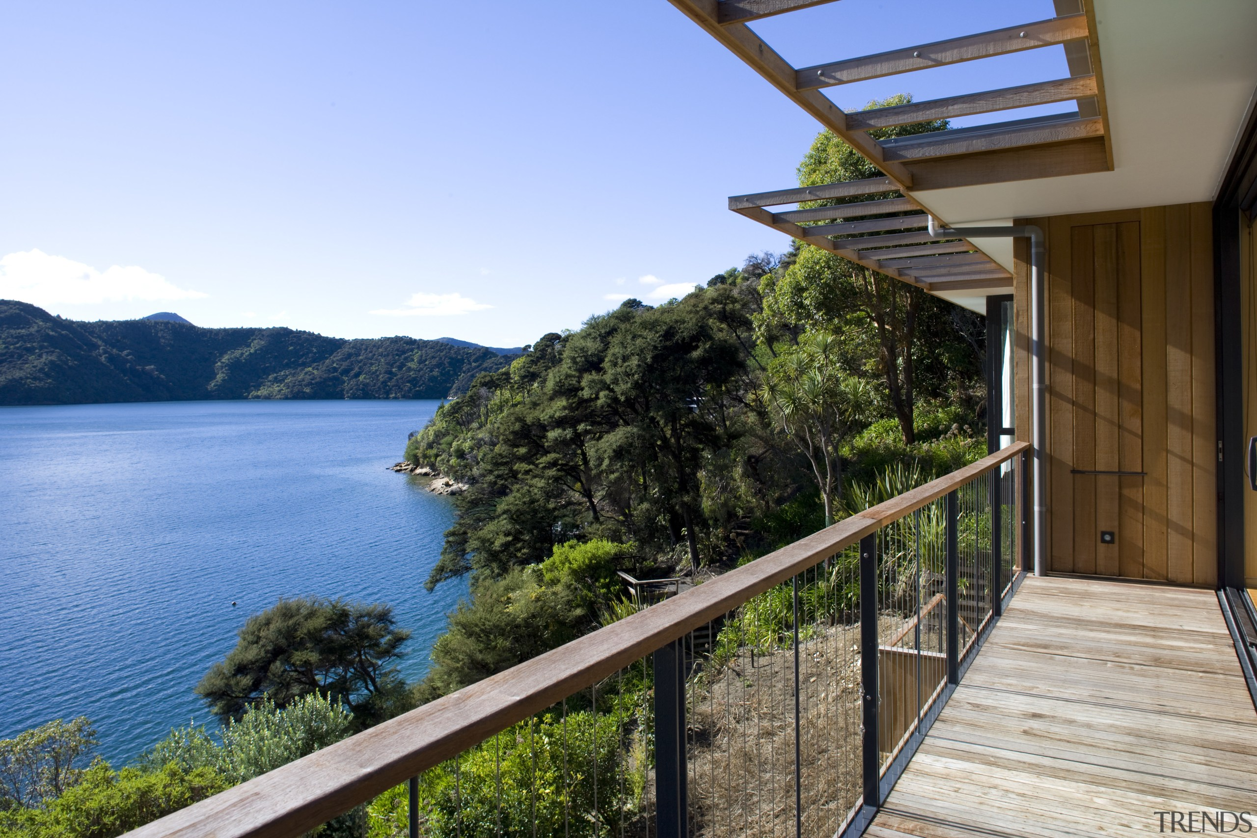 View of deck and side of house with cottage, estate, home, house, property, real estate, sky, tree, villa, water, teal