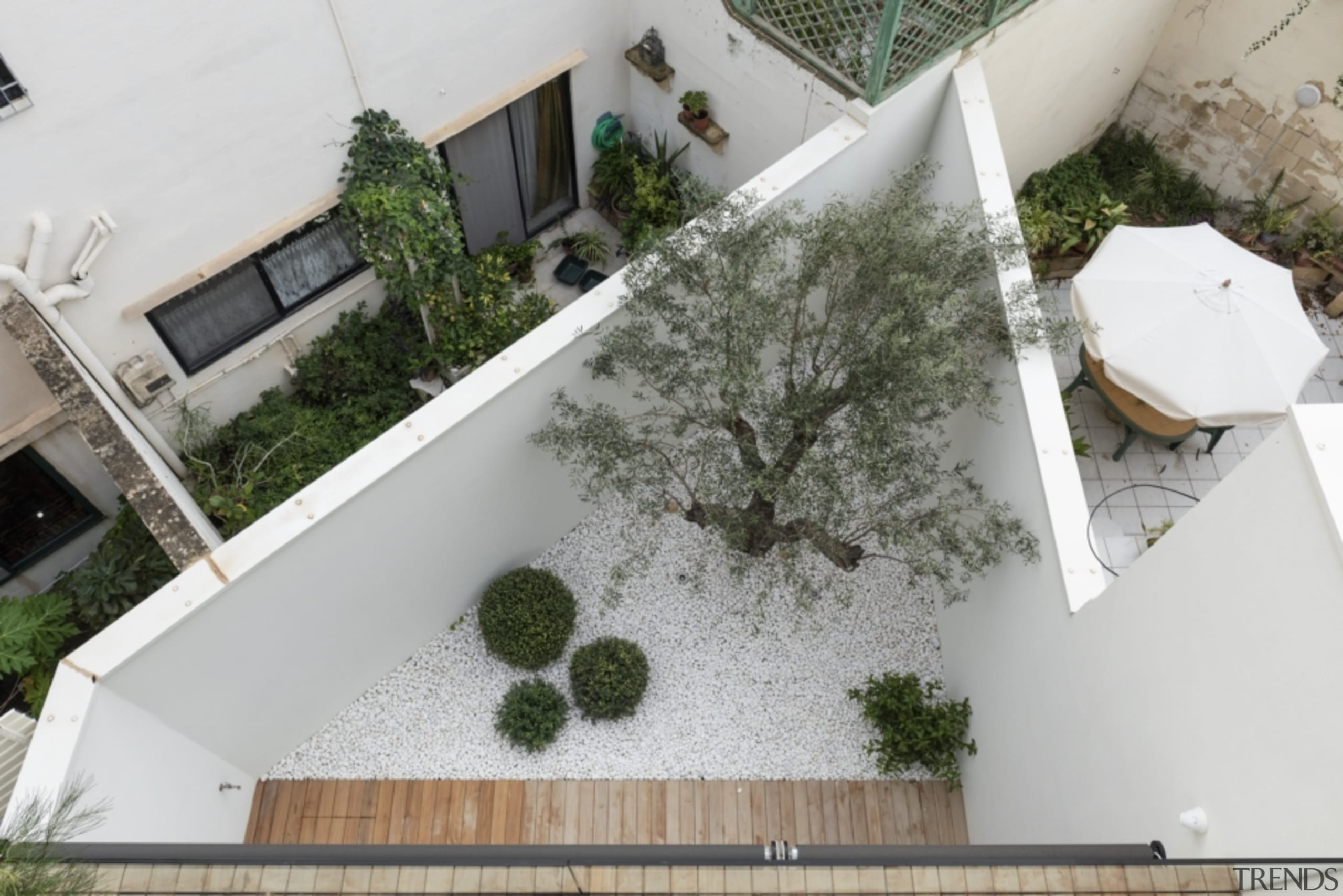 The home includes an outdoor courtyard at the architecture, building, courtyard, floor, grass, home, house, landscape, plant, property, real estate, roof, room, urban design, gray, outdoor living