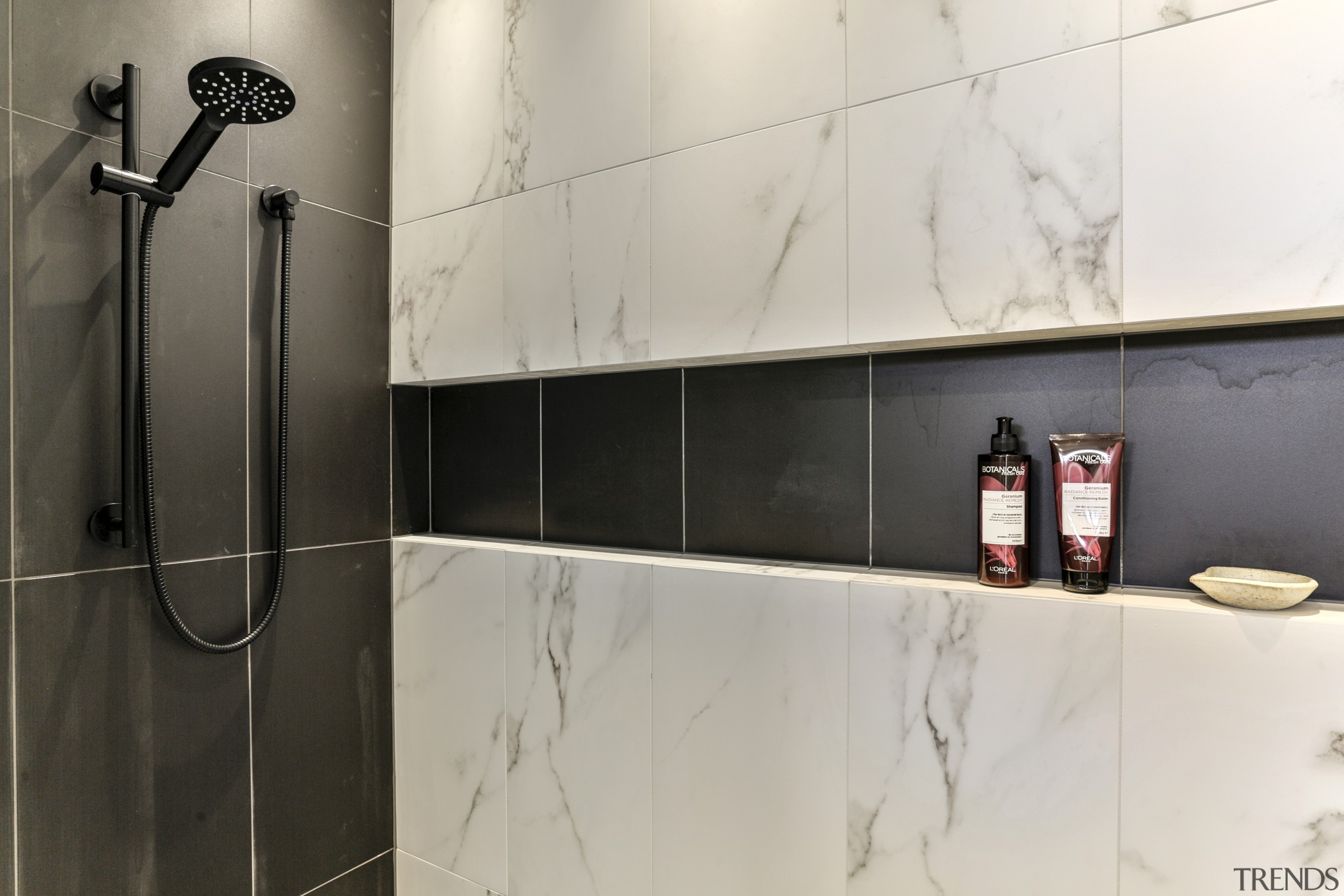 A long, walk-in shower stall allows for an gray, black