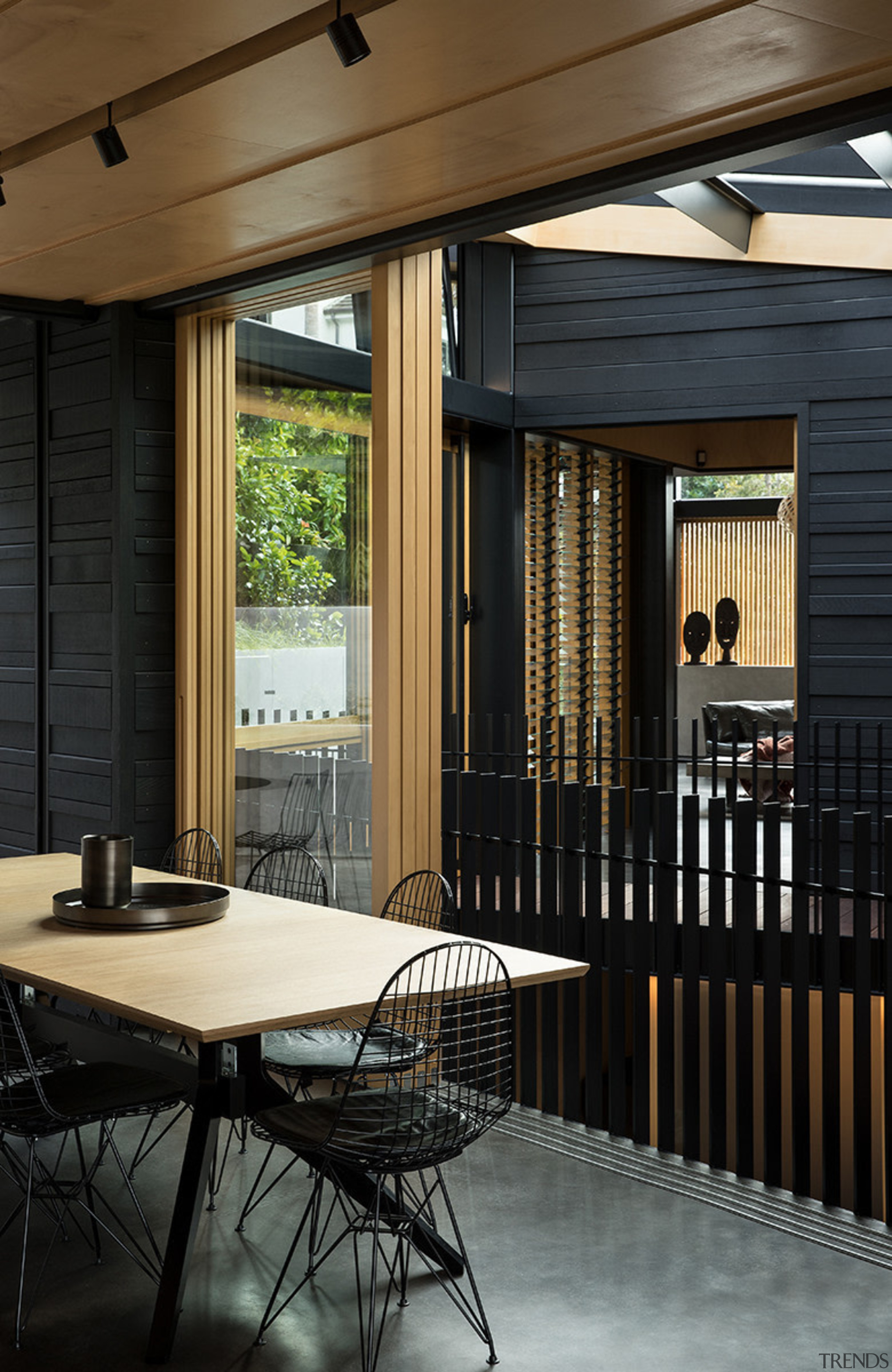 This central kitchen and accompanying dining area follows architecture, home, house, interior design, patio, porch, window, wood, black, Strachan Architects,