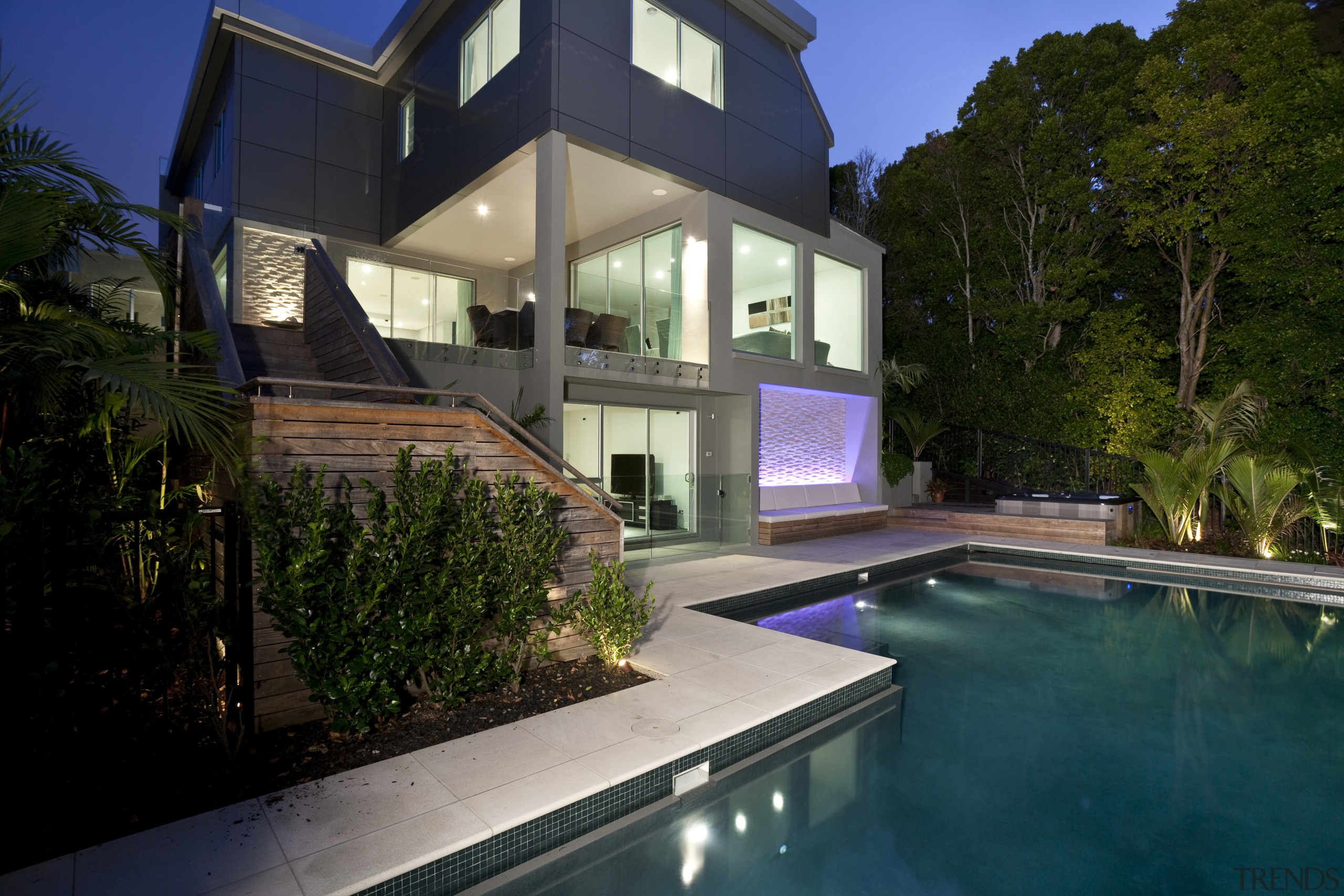 View of sleek poolscape with textured stone wall, architecture, backyard, estate, facade, family car, home, house, lighting, property, real estate, residential area, swimming pool, villa, window, black