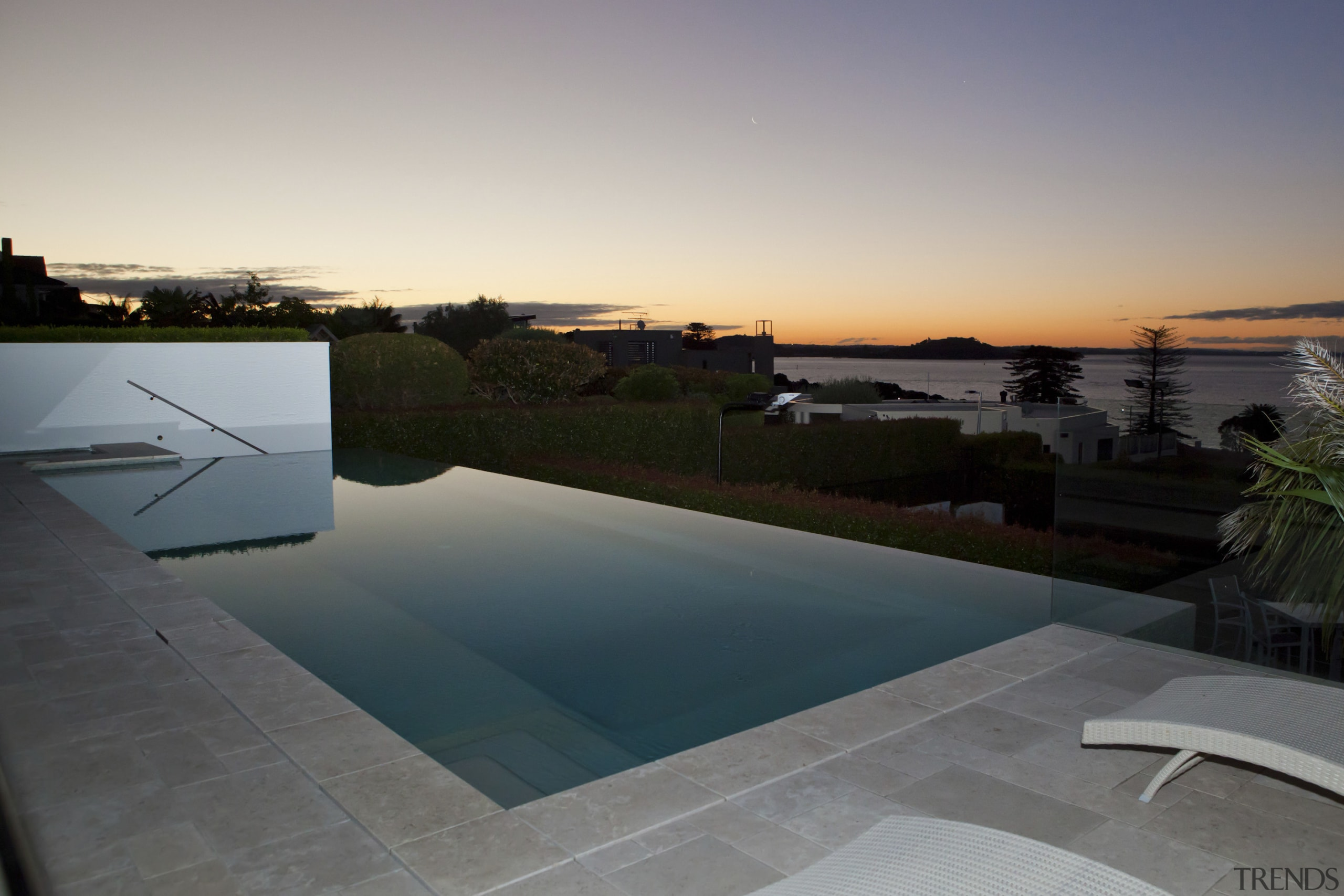 Evening sunset over the pool. - Evening sunset architecture, estate, evening, home, house, morning, property, real estate, reflection, roof, sky, sunlight, swimming pool, water, gray, black
