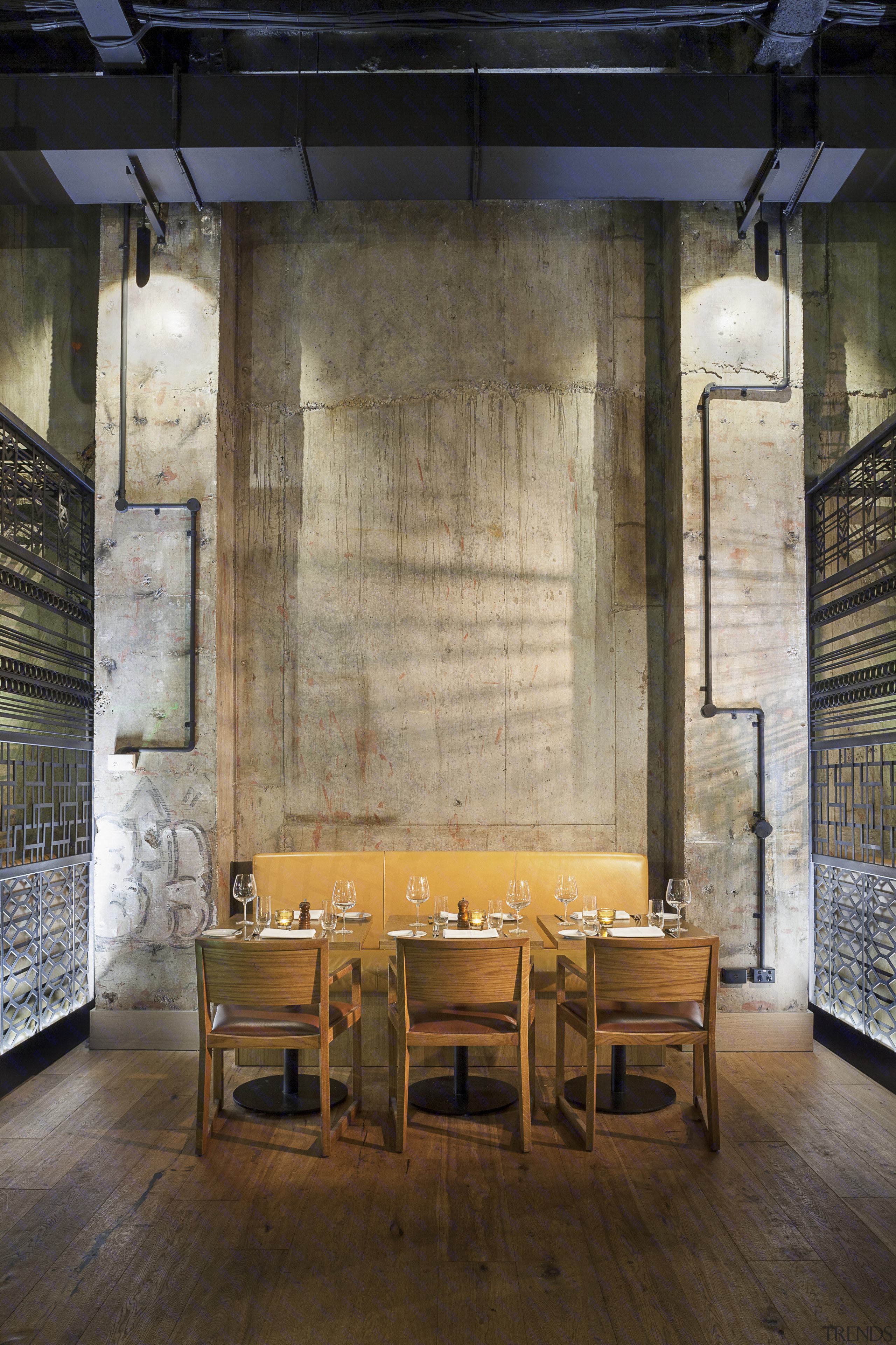 Stripped-back concrete walls and exposed services heighten the architecture, furniture, interior design, table, wall, wood, brown