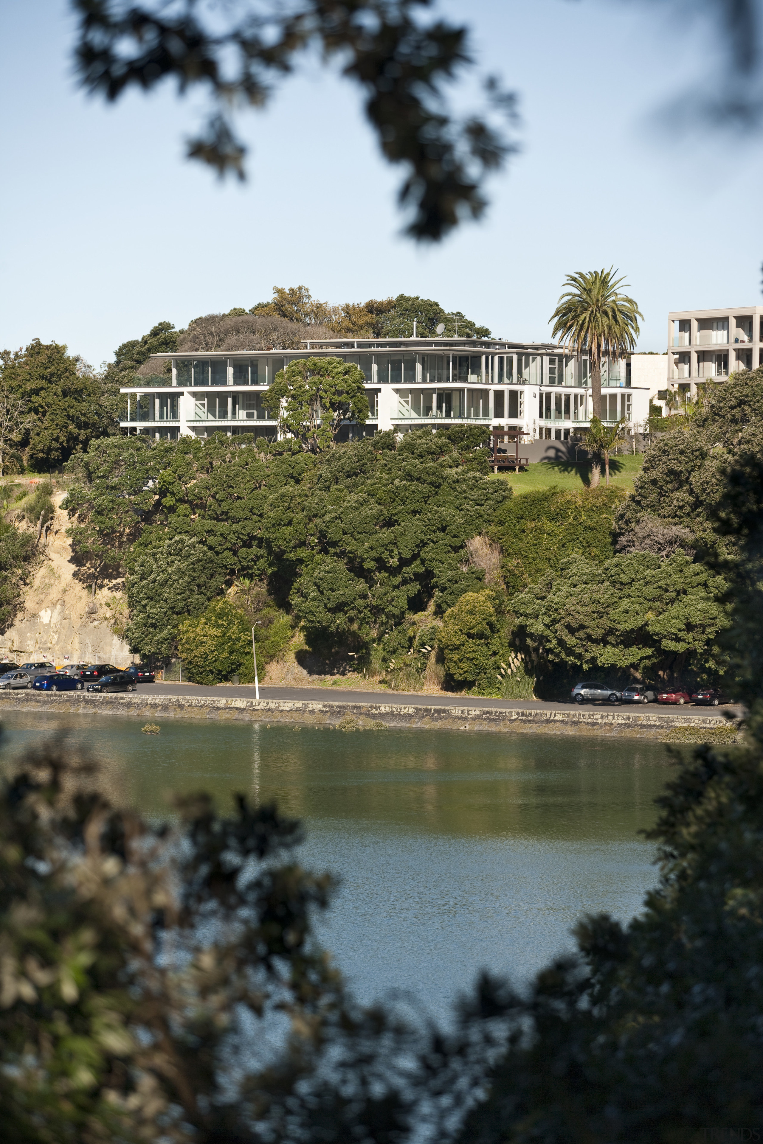 View of a large apartment development in Auckland city, estate, garden, house, lake, leaf, nature, plant, reflection, sky, tourist attraction, tree, water, brown
