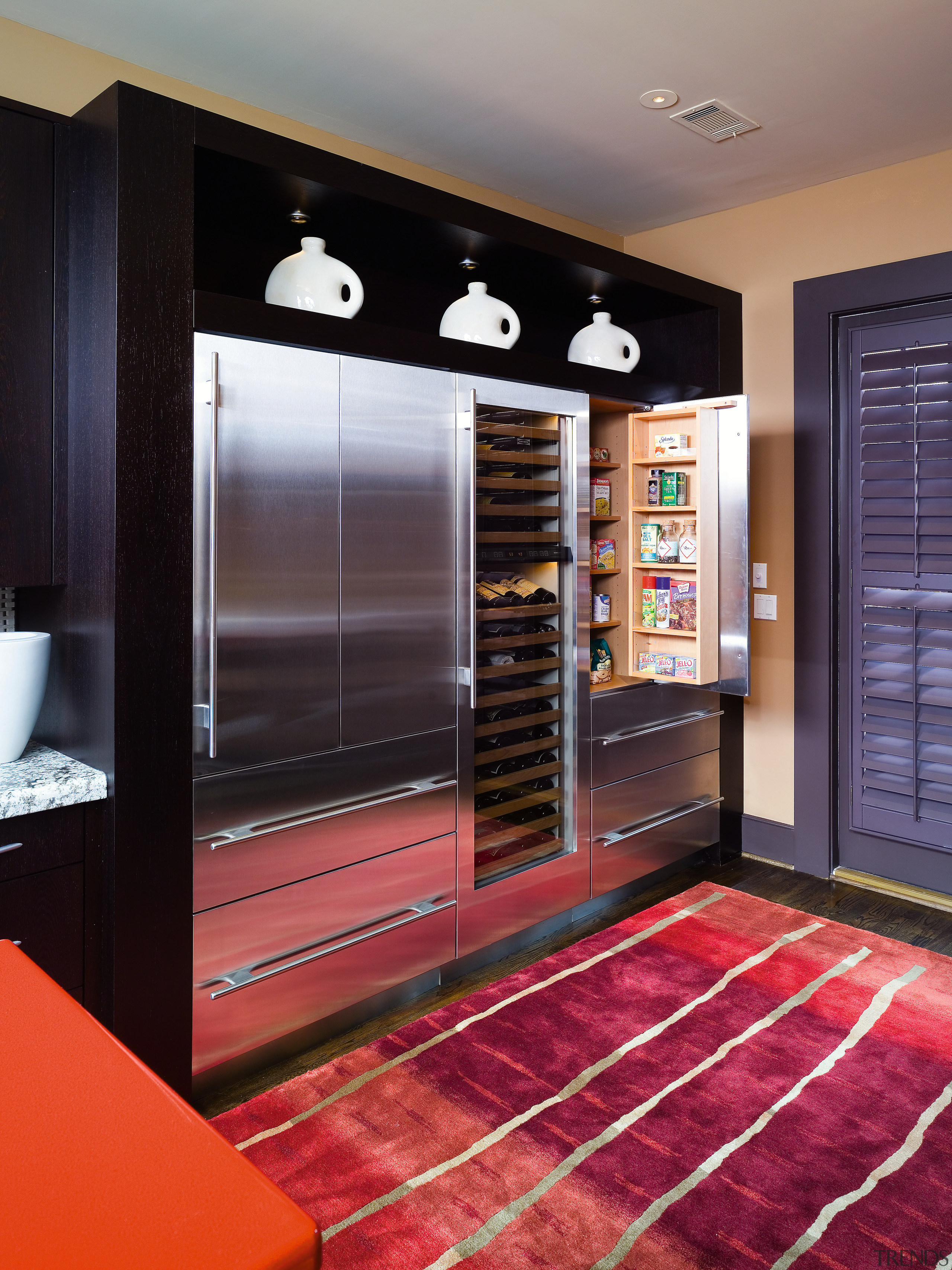 A view of this kitchen featuring black cabinetry, flooring, furniture, interior design, kitchen, room, black, red