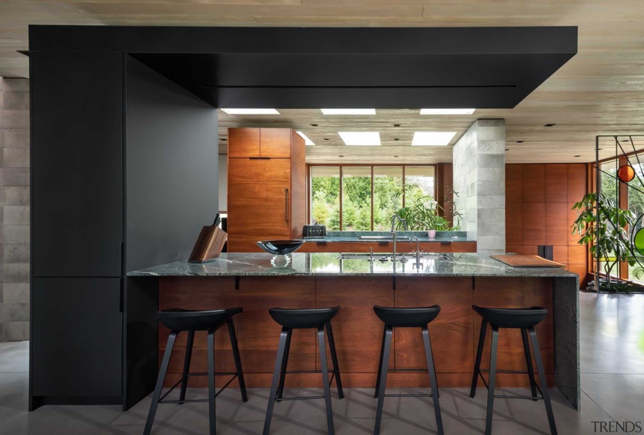 The kitchen island is framed by a wrap-over architecture, bar stool, building, cabinetry, ceiling, countertop, design, dining room, floor, flooring, furniture, hardwood, home, house, interior design, kitchen, kitchen & dining room table, lighting, material property, plywood, property, real estate, room, stool, table, tile, wood stain, black