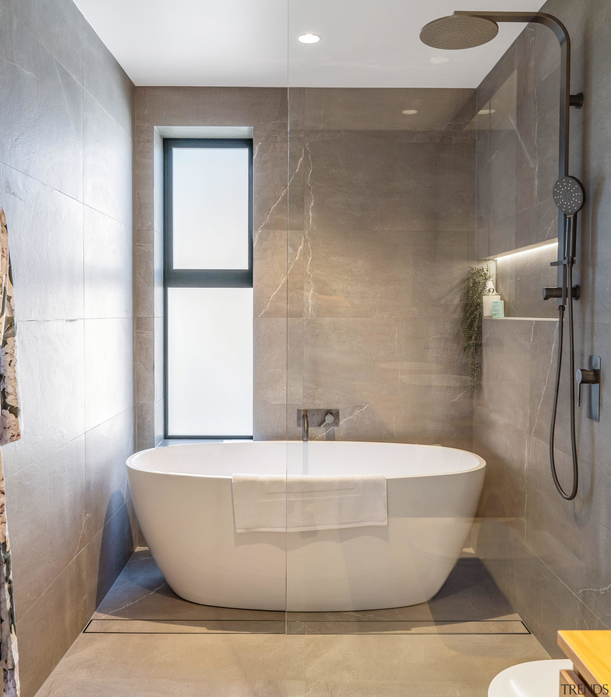 The freestanding tub is situated at the end