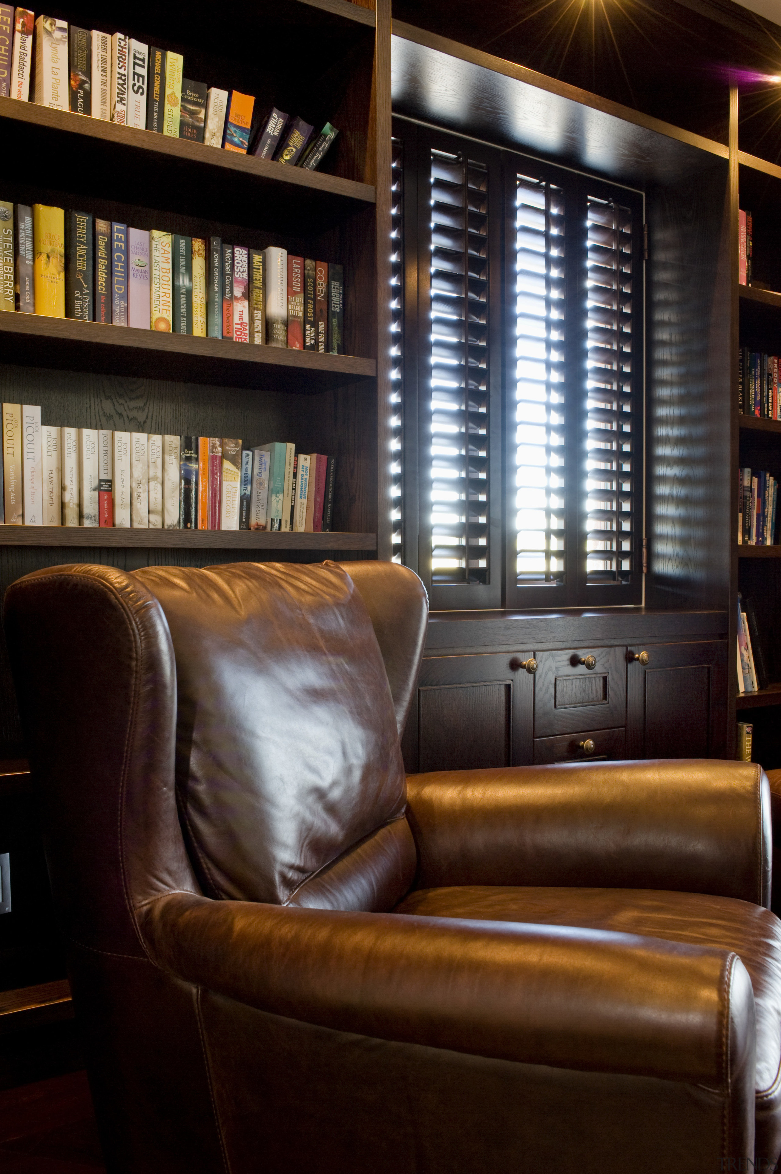 Image of dark stained library shelving and cabinetry bookcase, chair, furniture, home, interior design, library, living room, shelving, window, wood, black