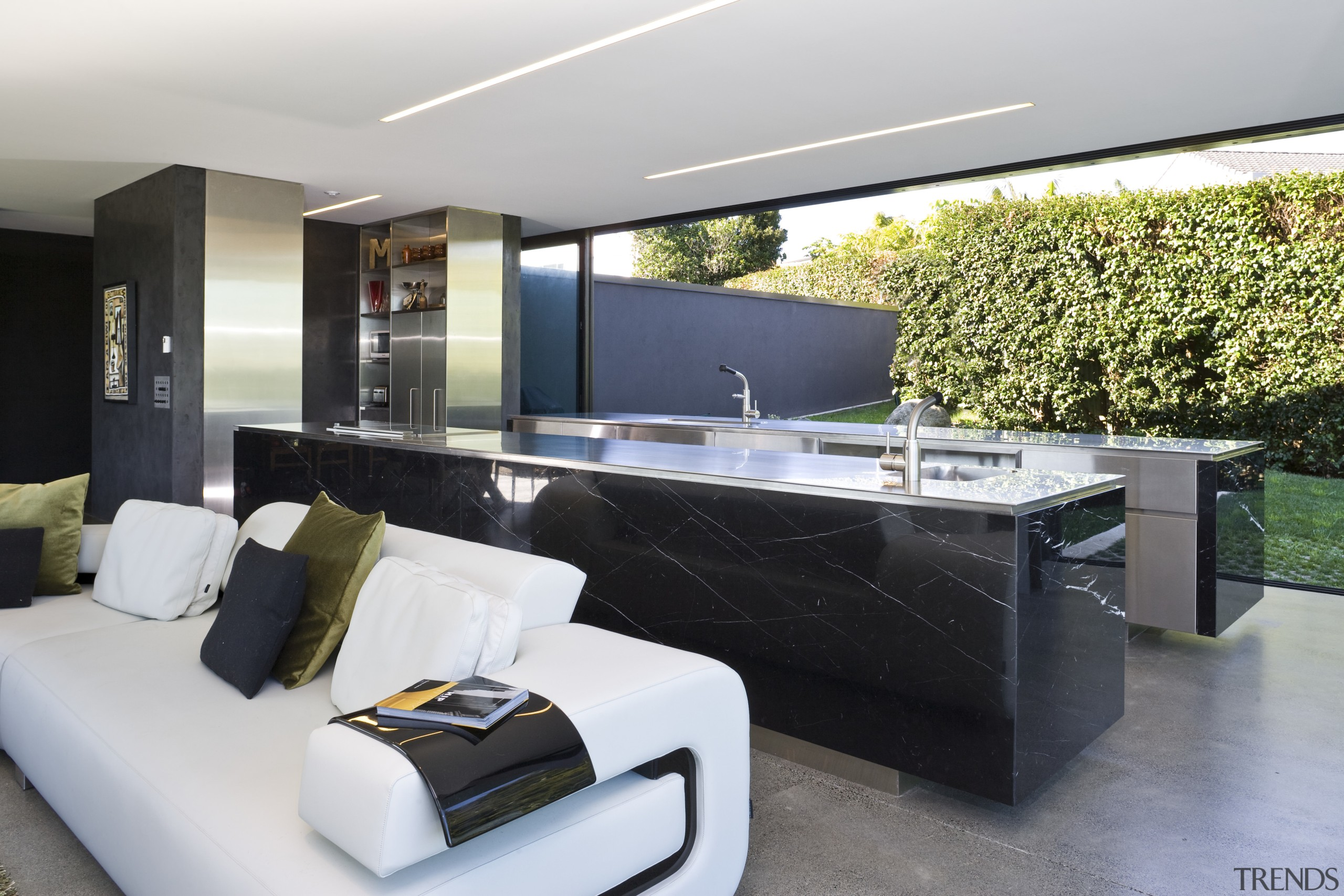View of open-plan kitchen and living area featuring interior design, living room, real estate, gray, black