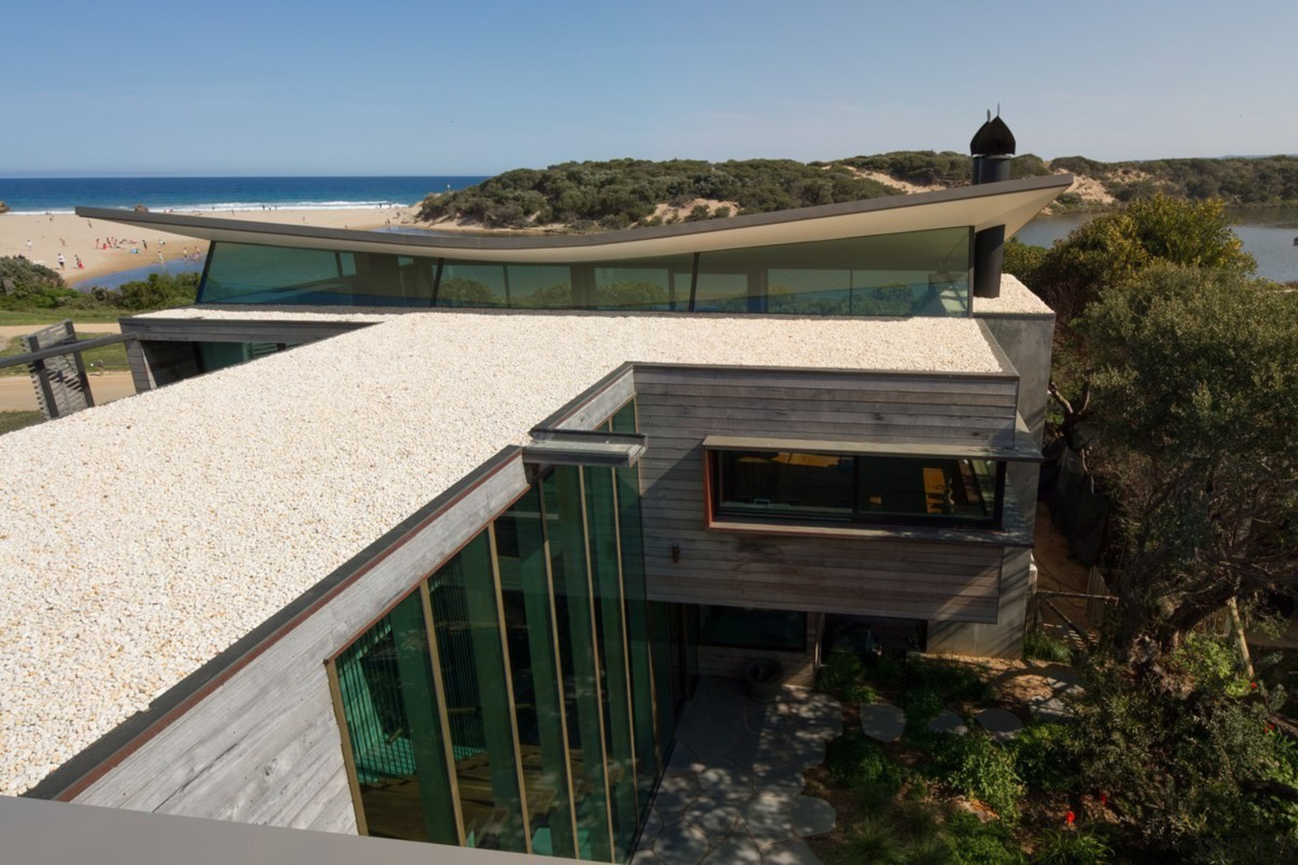 You can glimpse the beach nearby - You architecture, home, house, property, real estate, roof, black