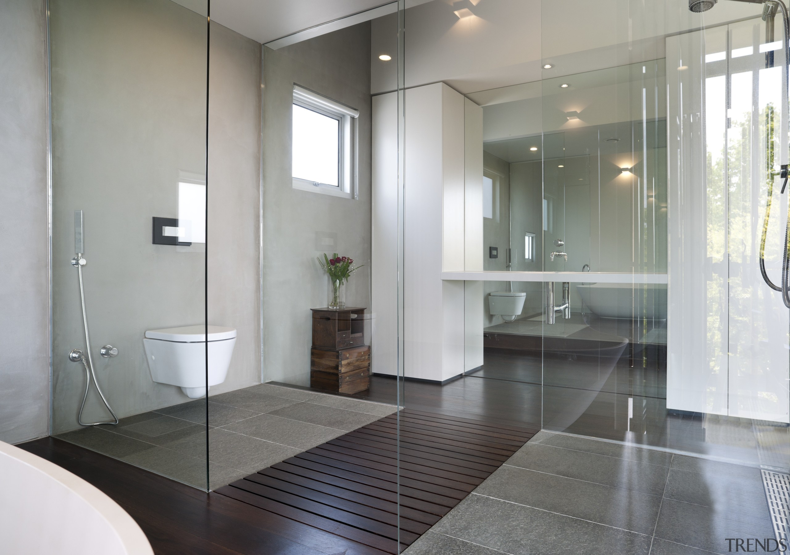 The toilet and shower in this contemporary master bathroom, floor, flooring, glass, interior design, property, real estate, room, sink, tile, wood flooring, gray