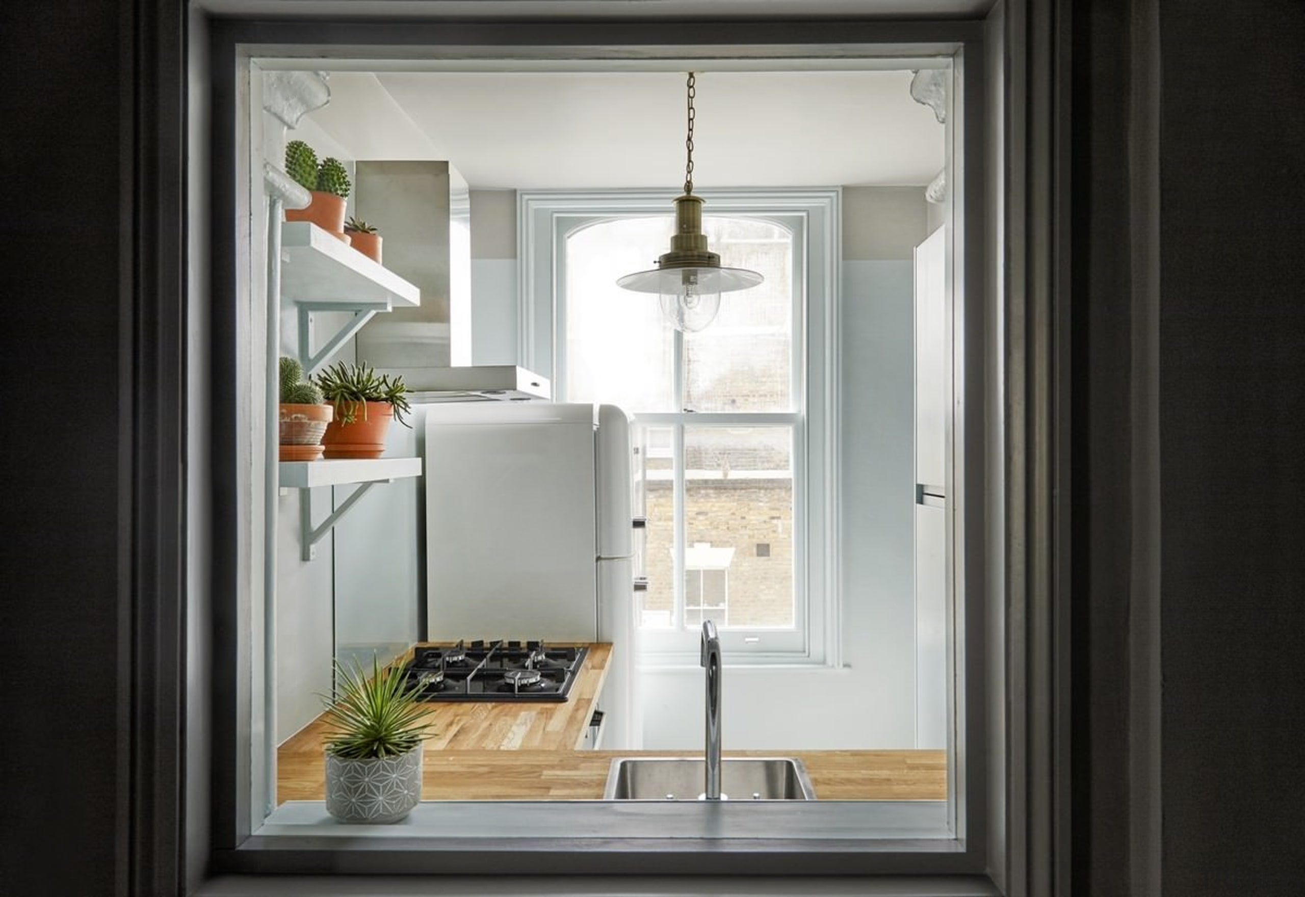 In the kitchen, a wood countertop creates a home, home appliance, interior design, window, black, gray
