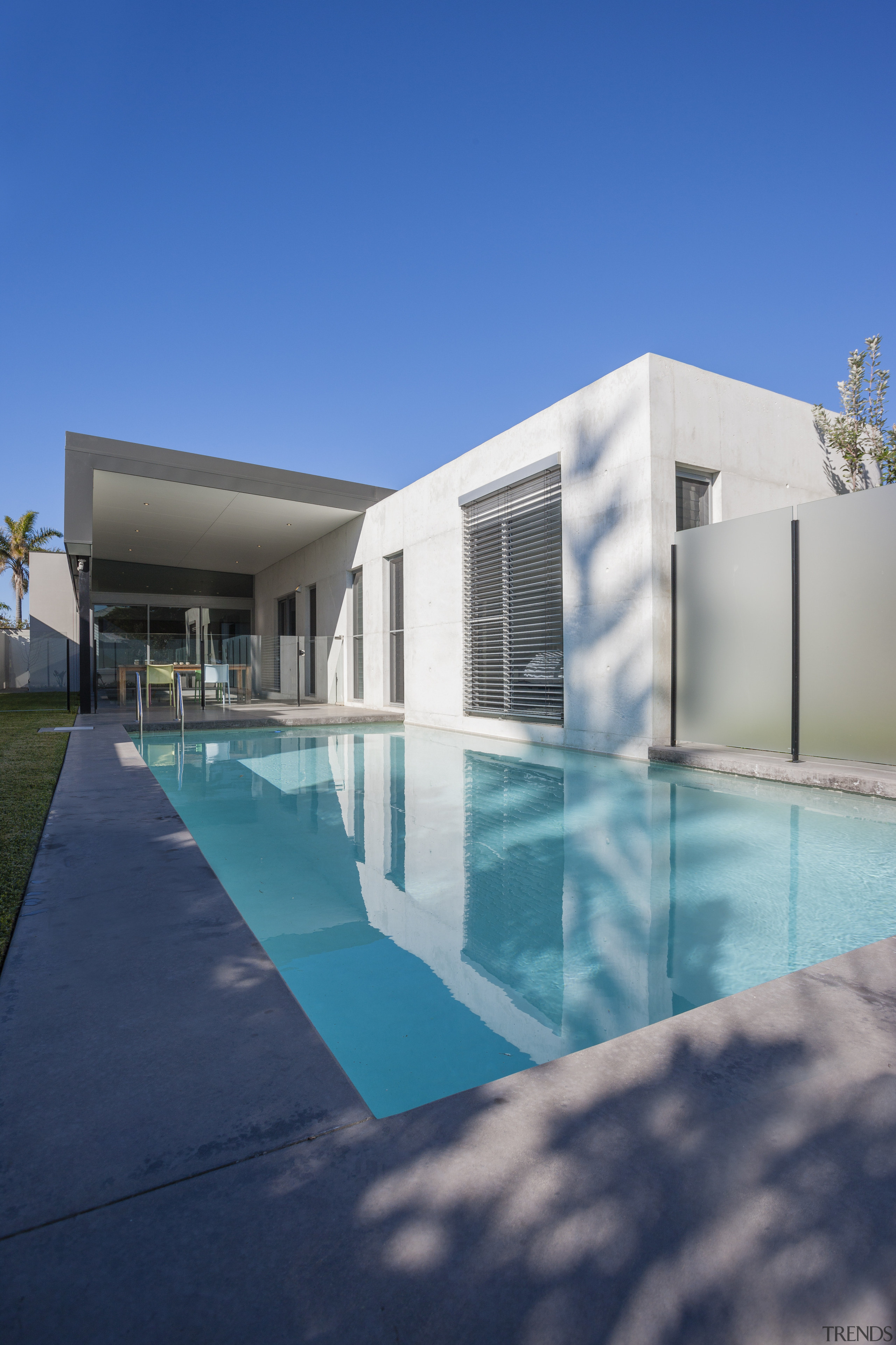 Shot of house from poolside. - Shot of architecture, elevation, estate, facade, home, house, leisure centre, property, real estate, reflection, sky, swimming pool, villa, water, blue, teal